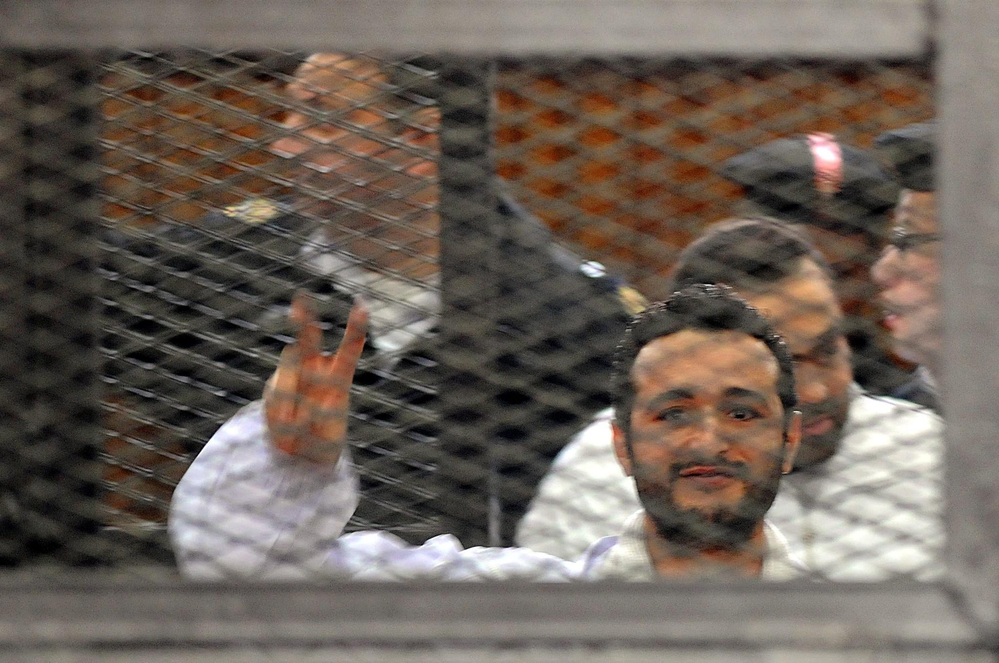 Egyptian activist Ahmed Douma signals to his supporters during his trial in Cairo.