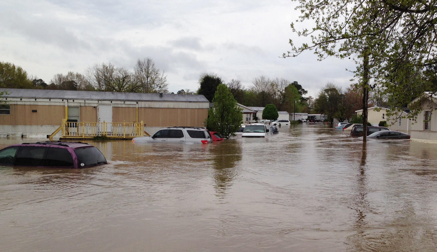 Flood waters cover a street in a mobile home park in Pelham, Ala., on Monday. Police and firefighters had to rescue people who were trapped by muddy, fast-moving water after storms dumped torrential rains in central Alabama.