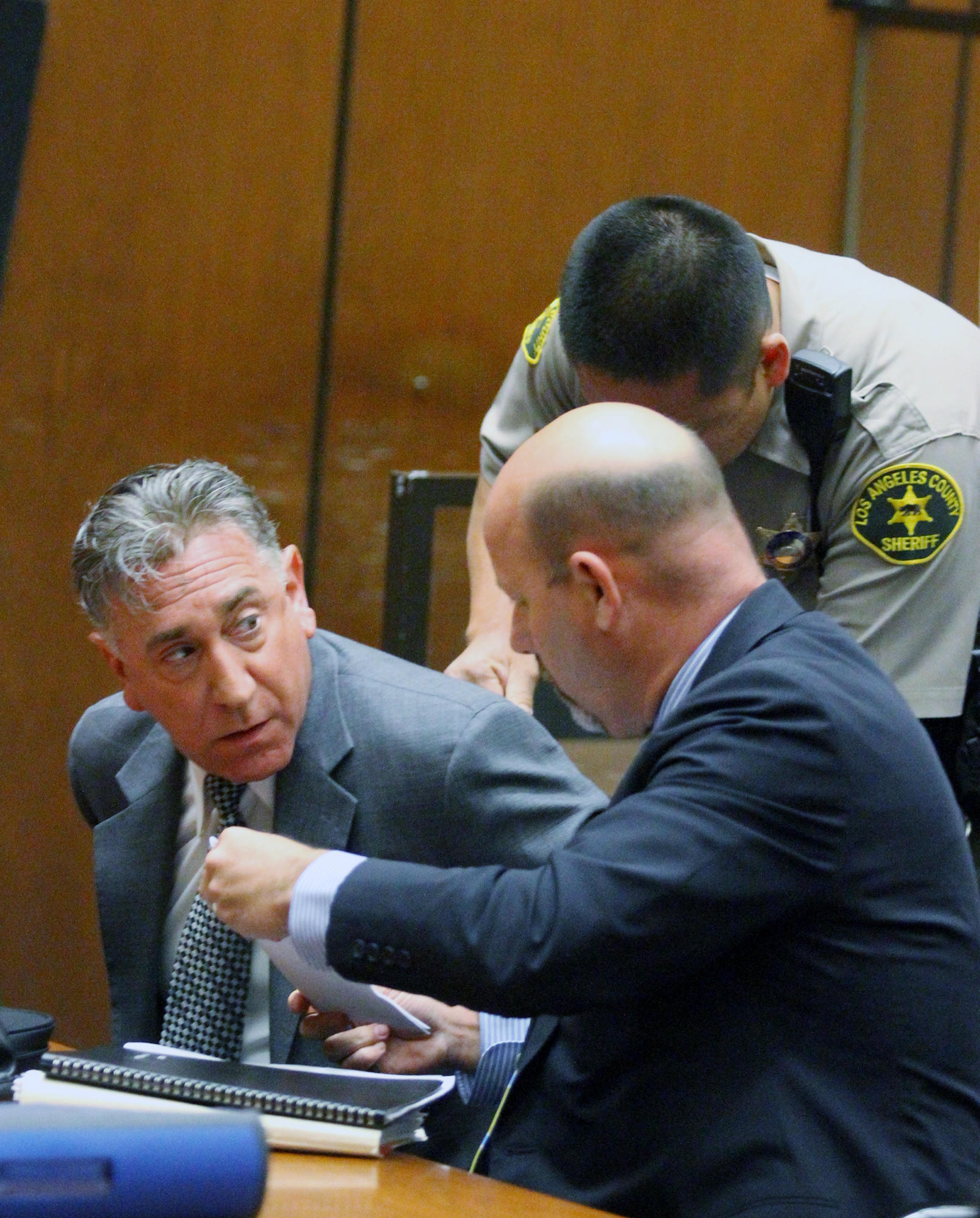 Former Glendale Mayor John Drayman, after he was sentenced to one year in Los Angeles County jail, is put in handcuffs by a Los Angeles County Sheriff's deputy with his lawyer Sean McDonald at his side at Superior Court in Los Angeles on Monday, April 7, 2014. Drayman was sentenced for embezzling proceeds from the Montrose Farmer's Market, and filing false tax returns. His sentence is 365 days in county jail, with 4 days credit for time served, and to pay restitution and all court fees.