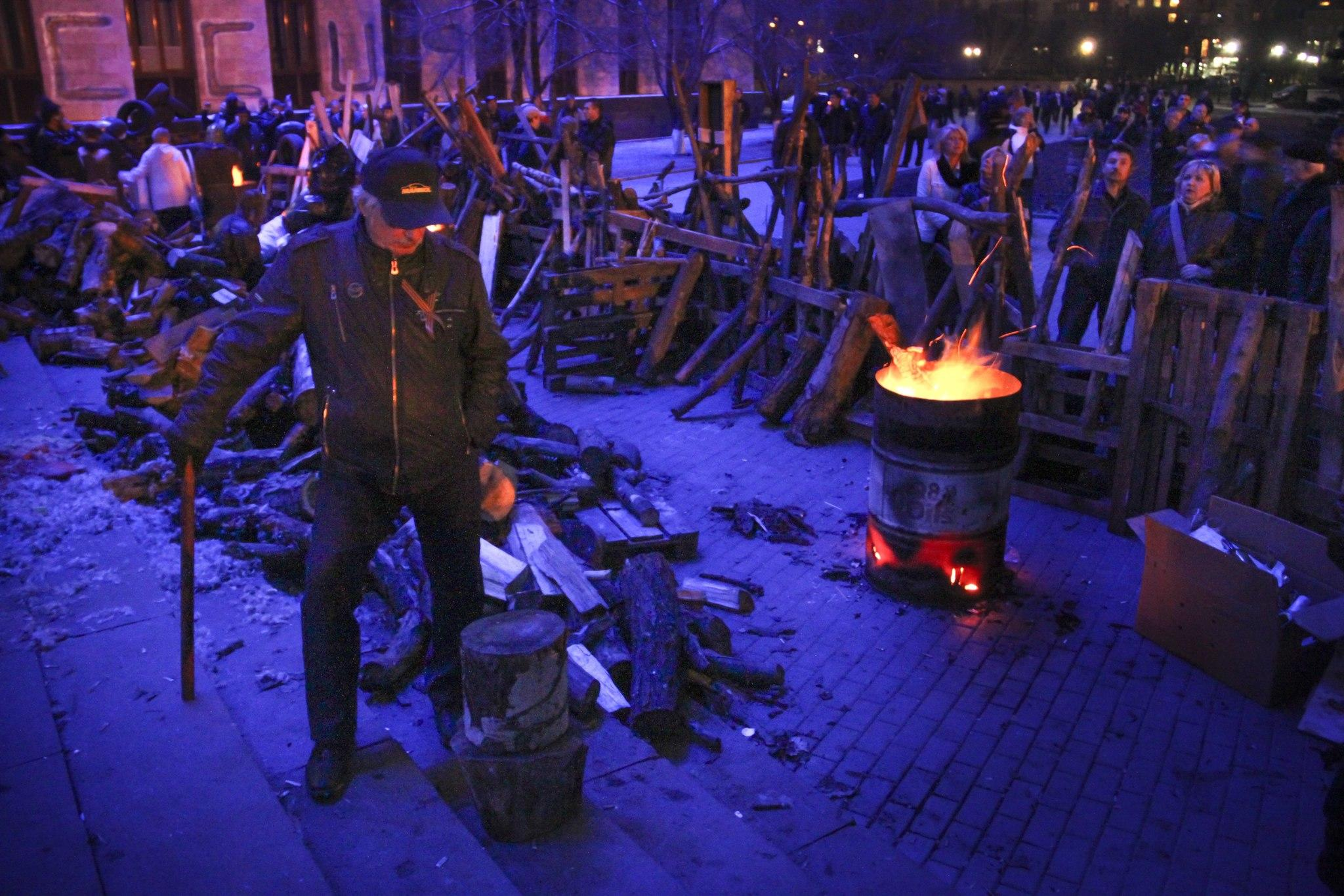 People gather near a barricade set up by protesters at the regional administration building in Donetsk, Ukraine.