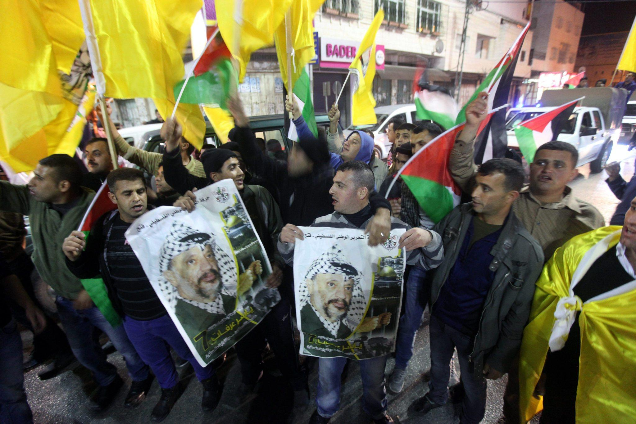 Palestinian supporters of the Fatah party carry posters of Yasser Arafat, the late Palestinian Authority president, in the West Bank city of Hebron. They were expressing support for a move by The Palestinian Authority to join 15 international bodies and conventions.