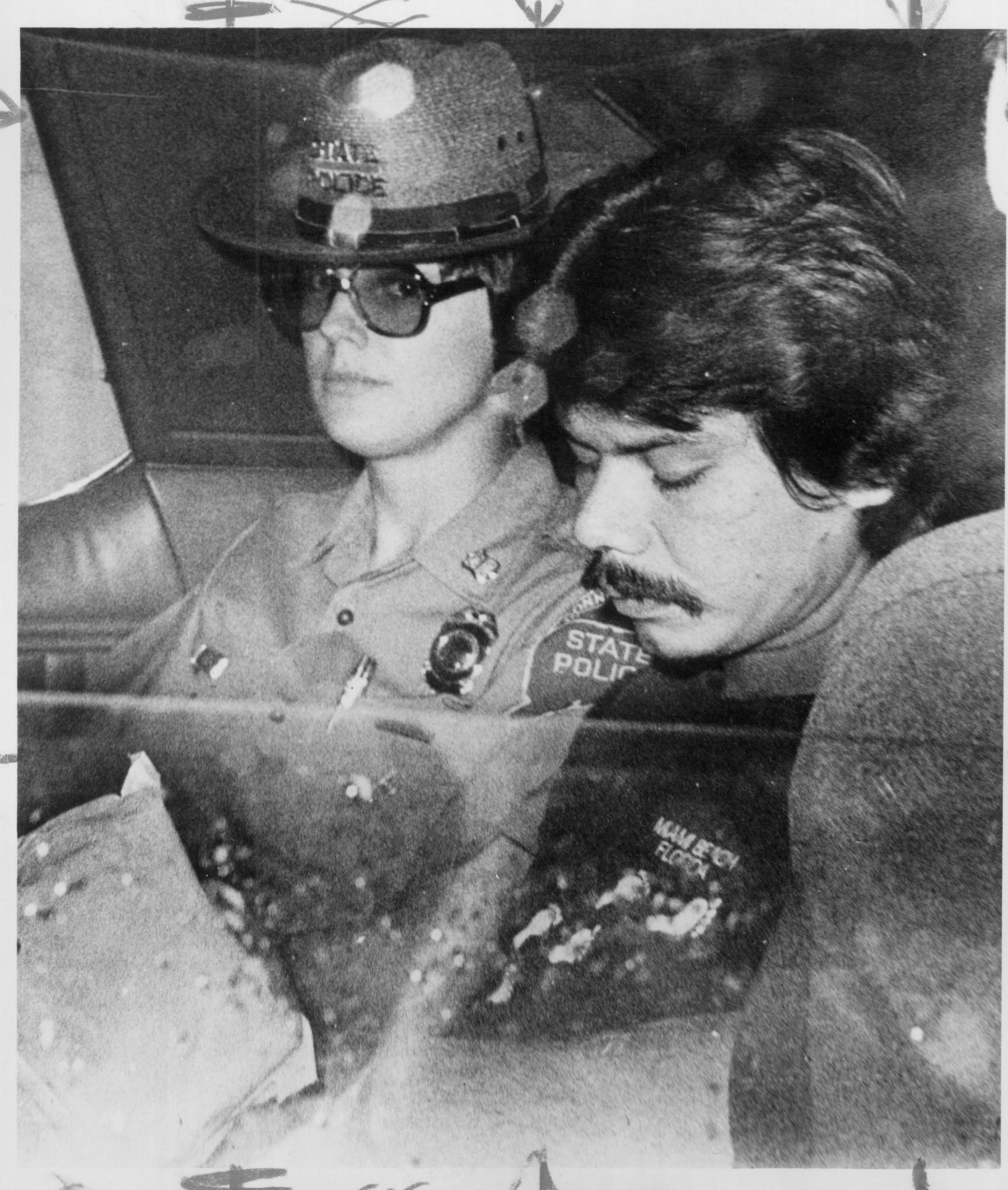 Lorne Acquin leaves Waterbury Superior Court escorted by state police Trooper Marjorie J. Kolpa after appearing for arraignment on nine counts of murder.