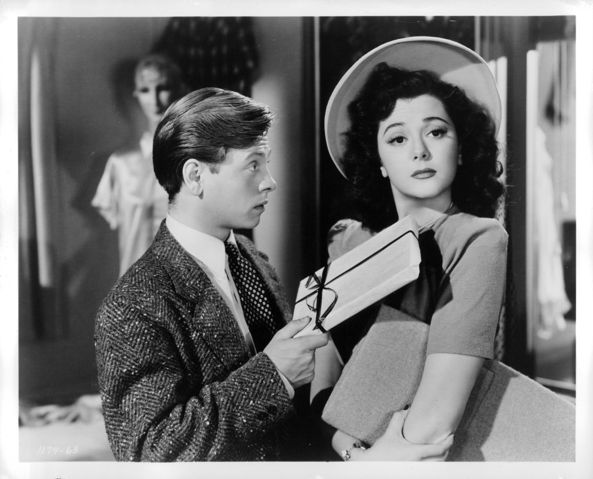 """Mickey Rooney hands a gift to Ann Rutherford in a scene from the film """"Andy Hardy's Private Secretary."""""""