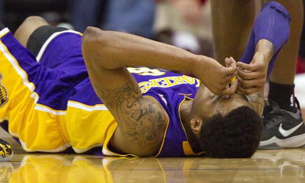 Lakers guard Kent Bazemore lies on the court after tearing a tendon in his right foot during Sunday's 120-97 loss to the Clippers at Staples Center.