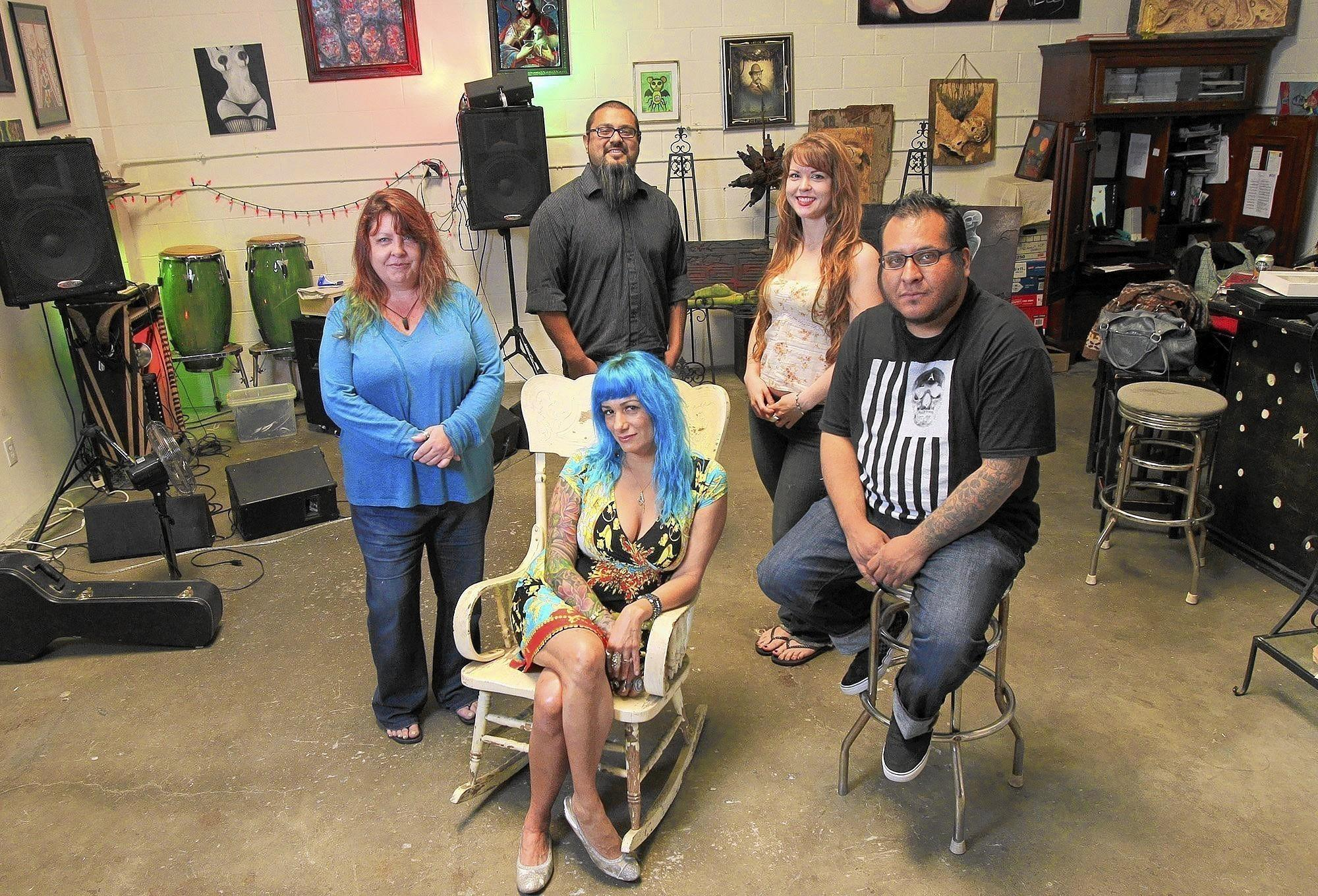 Owner Kat Monroe, center, poses for a photo with artists, counterclockwise from right, Vincent Gabriel, Carissa Martin, Michael Bermudez and Danaan McGregor at Sev Ven Gallery in Huntington Beach.