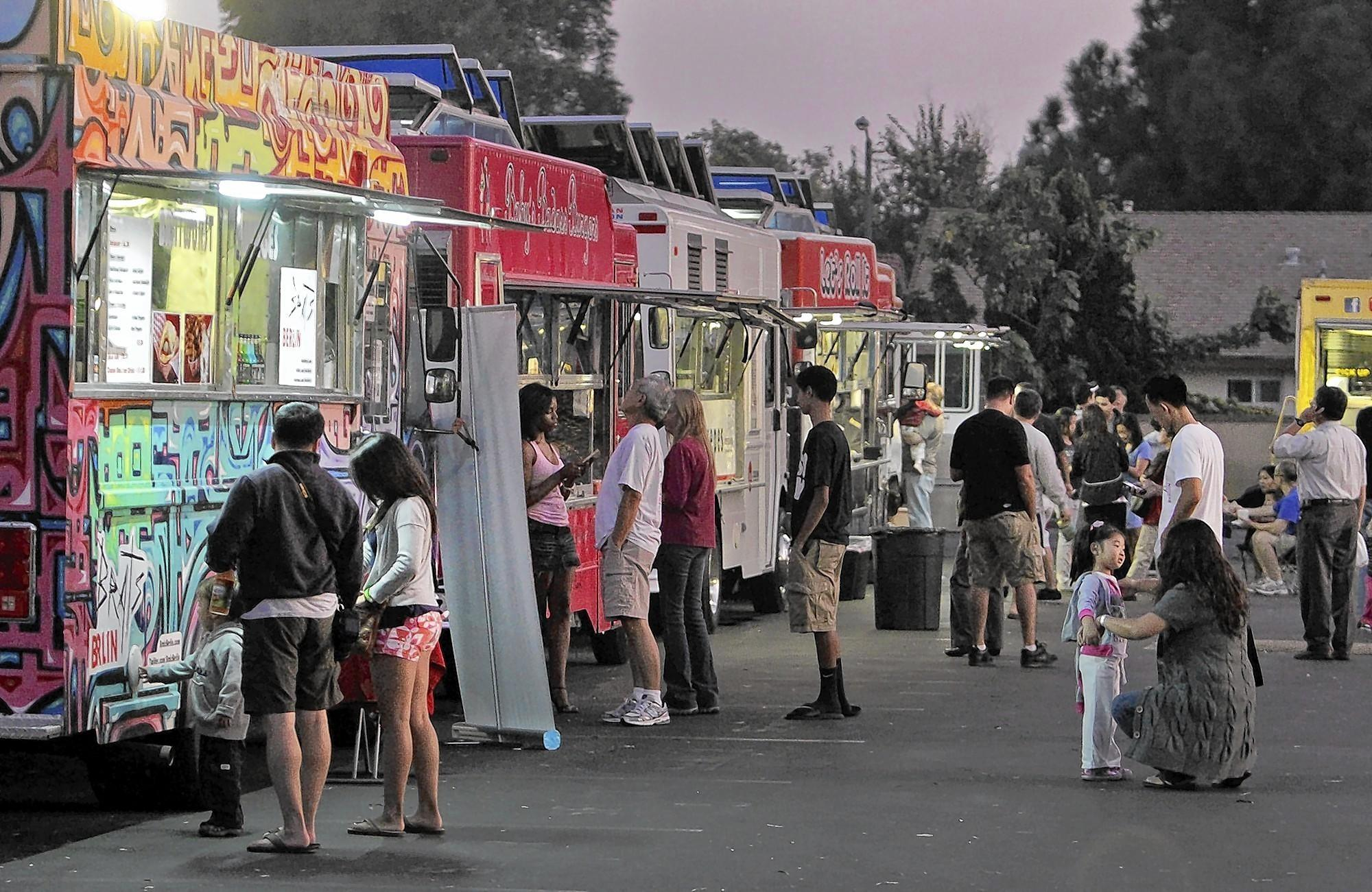L.A. County health inspectors often don't know where specific food trucks and carts can be found, making surprise inspections impossible. Such unannounced inspections are routine for restaurants. Above, food truck vendors in Cerritos in 2011.