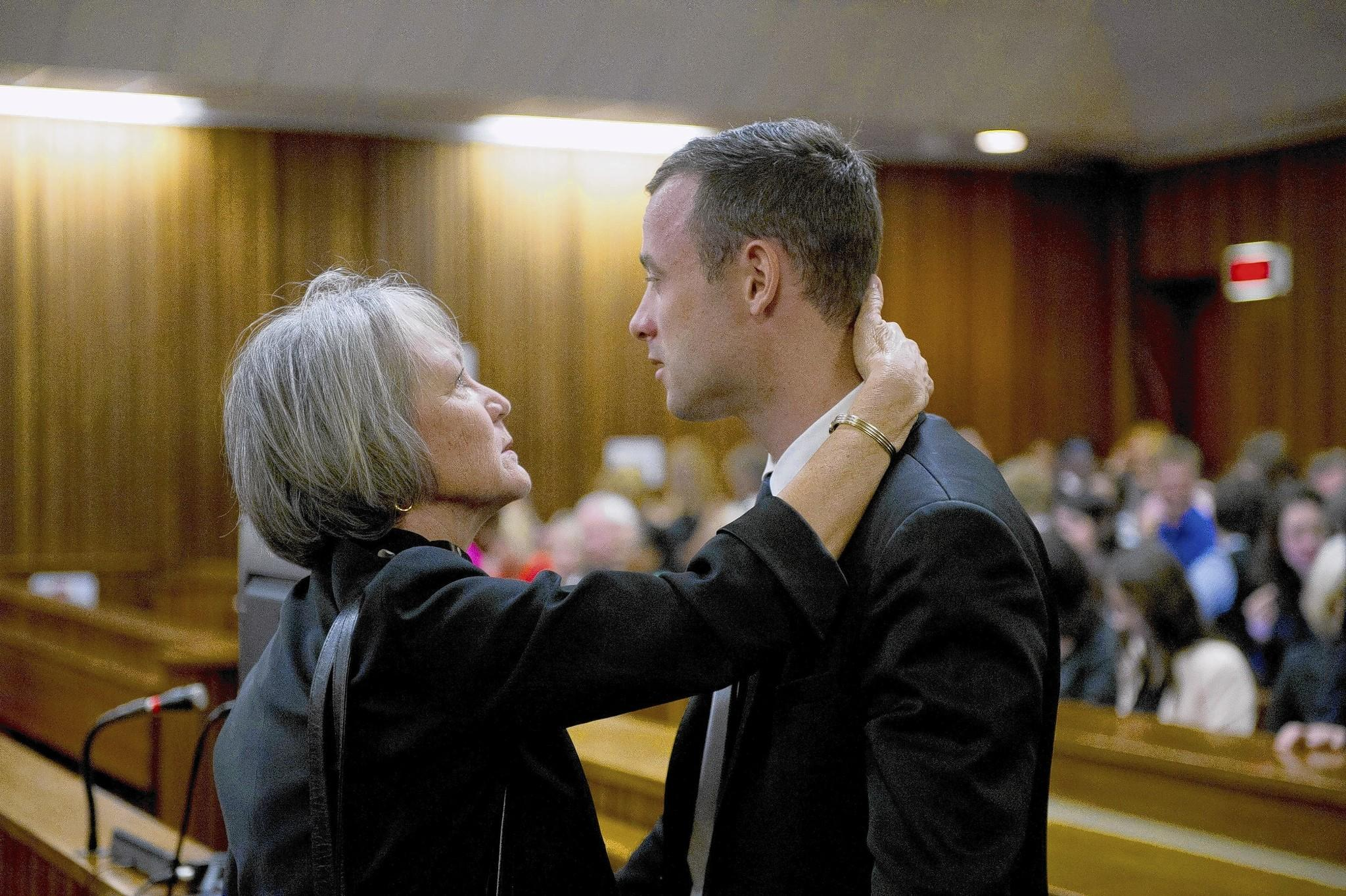 South African Olympian Oscar Pistorius speaks with a family member during his trial in Pretoria, South Africa. He has pleaded not guilty to murder in the death of his girlfriend, Reeva Steenkamp. He has said he mistook her for an intruder before shooting through a door in his apartment.