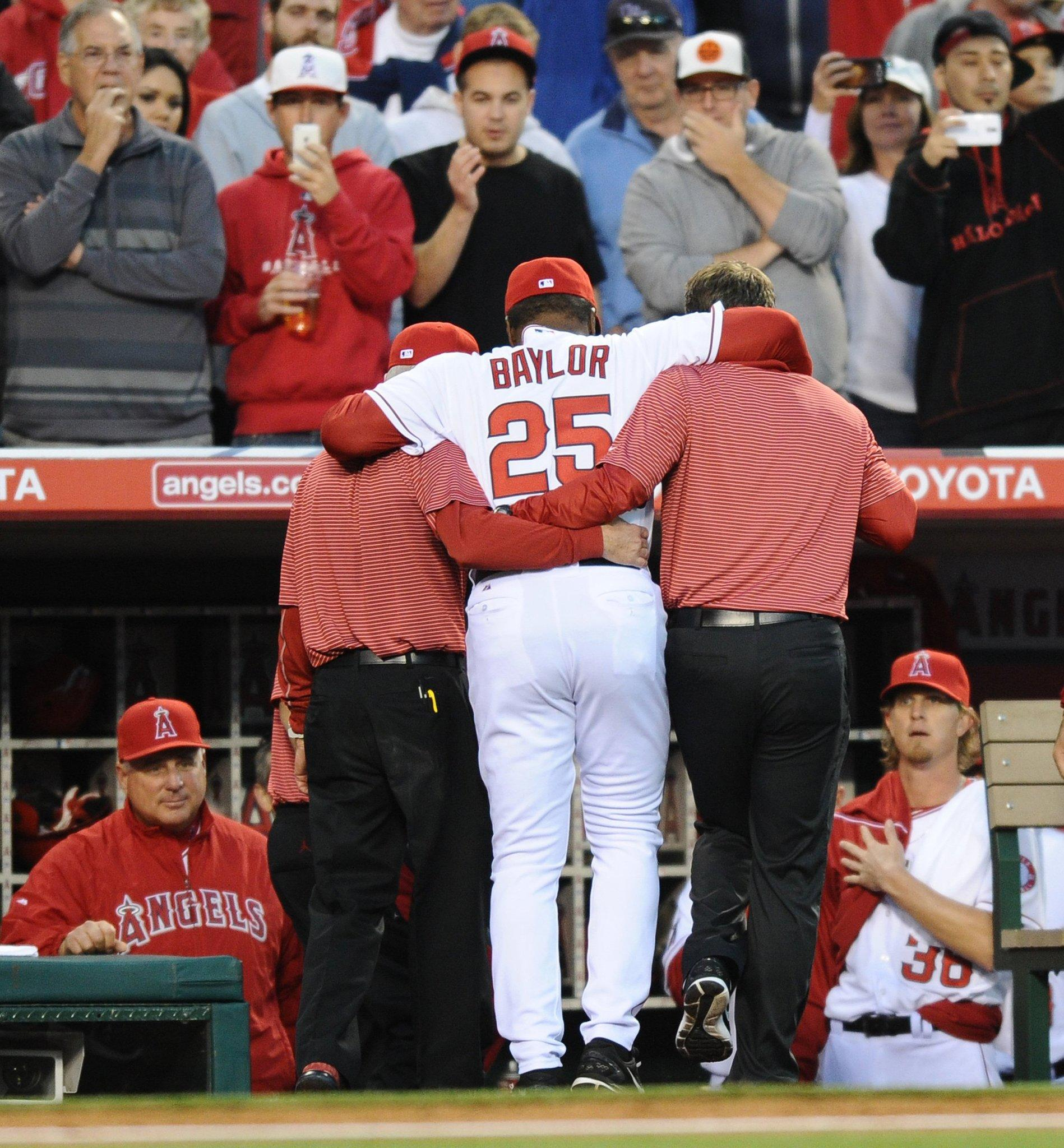 Angels coach Don Baylor injured his leg while catching the first pitch on Opening Day.