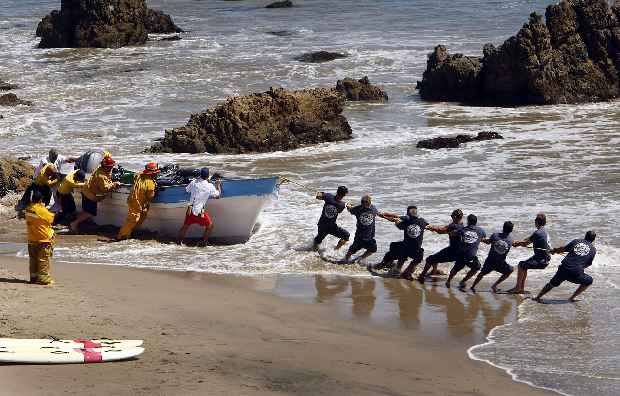 Firefighters pull a beached panga-style boat back into the water at Leo Carrillo State Beach in Malibu on Monday. The boat was seized after it washed ashore. Authorities said it was loaded with as much as a ton of marijuana.