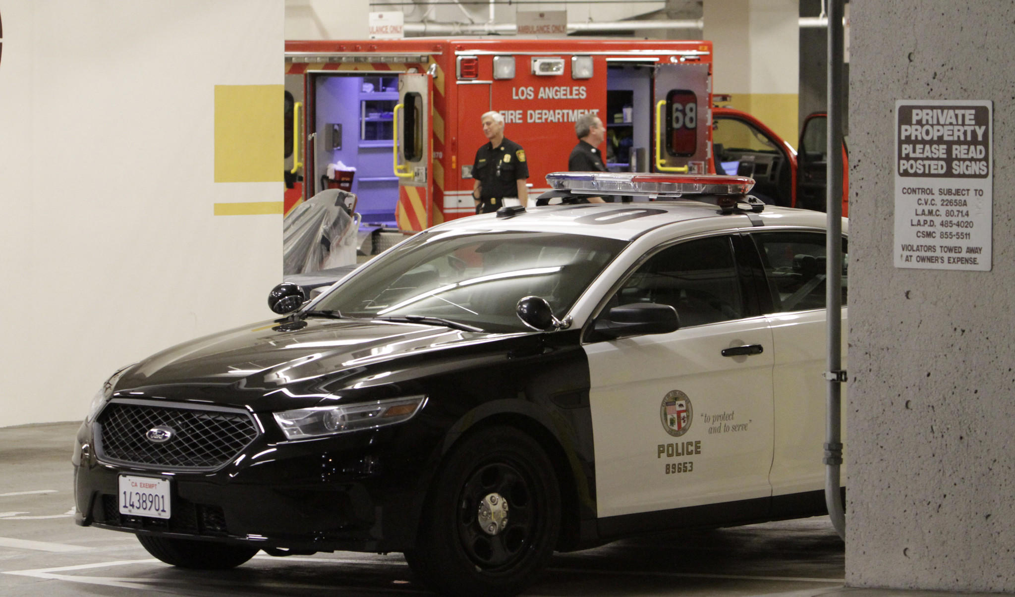 An ambulance and LAPD patrol car are shown at the emergency entrance at Cedars-Sinai Medical Center, where the wounded officer was taken.