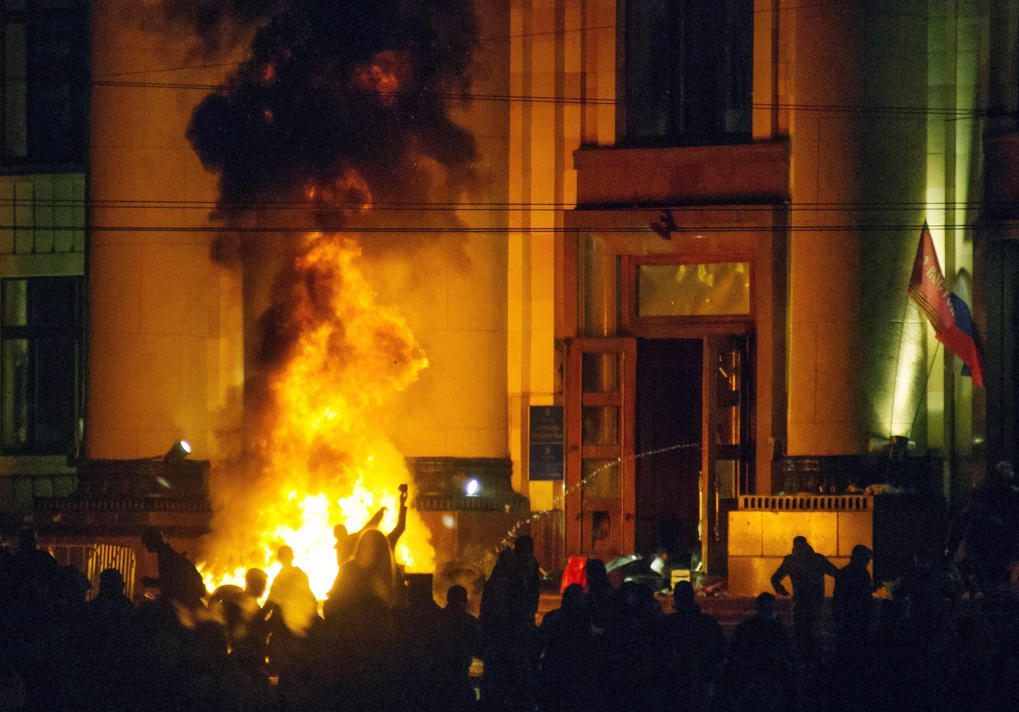 Pro-Russia protesters burn tires near a regional administration building in Kharkiv, Ukraine, in a clash with riot police for control of the building.