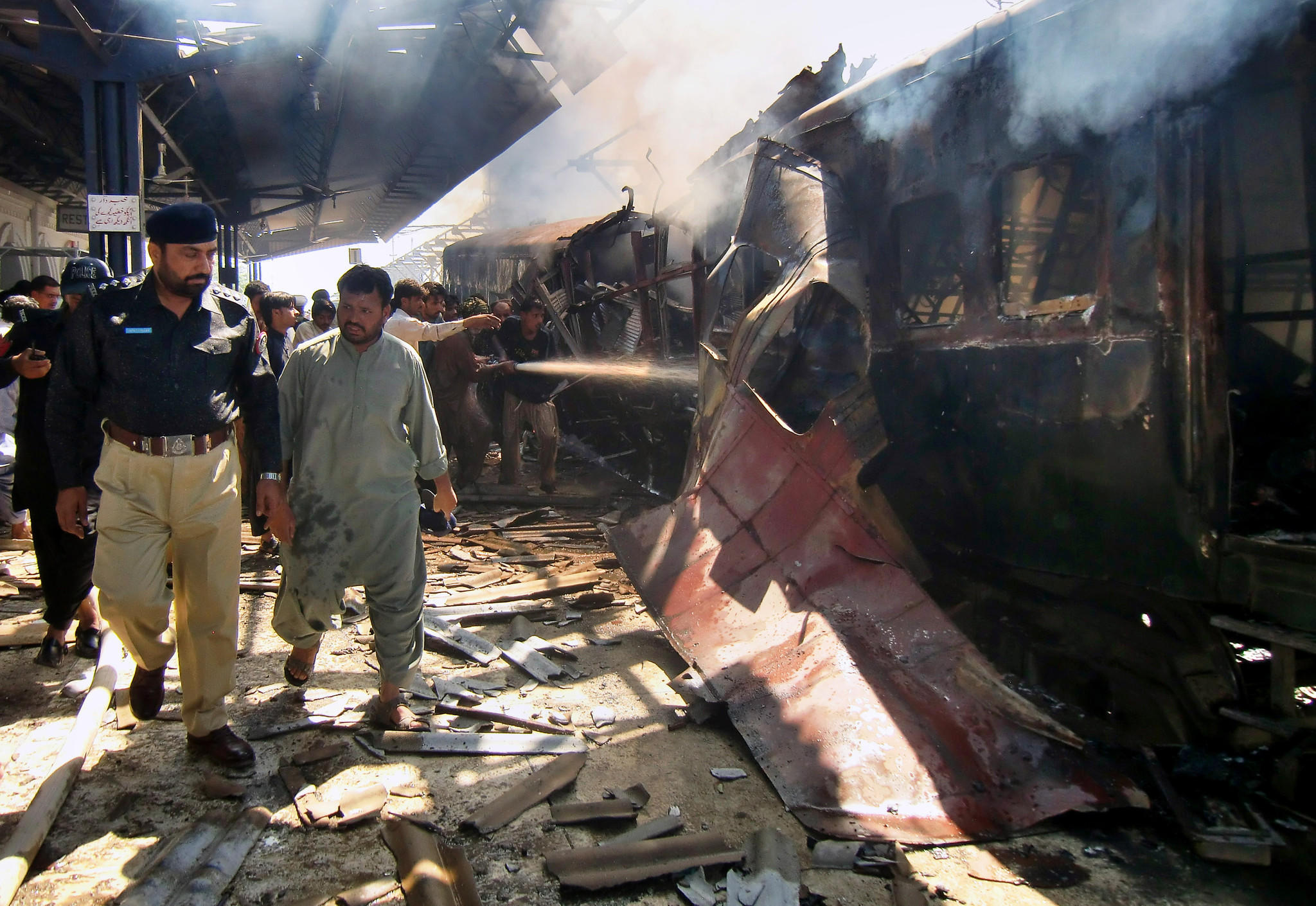 A police officer investigates as firefighters try to extinguish the flames after a train bombing in Pakistan's southwestern province of Baluchistan.