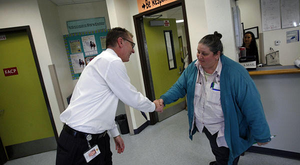 Los Angeles Unified School District superintendent John Deasy, left, shakes hands with senior office tech Bonnie Sugerman at John H. Liechty Middle School.