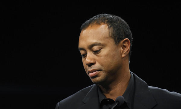 Tiger Woods looks down during a news conference in Washington on March 24. Woods will miss the Masters for the first time in his career after having surgery on his back.