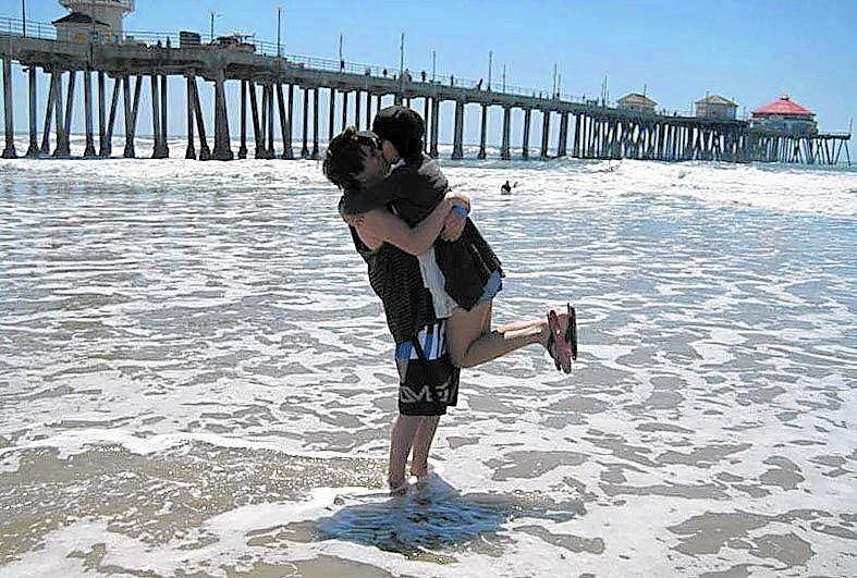 The young couple Jon Ludlow and Ivy Ho embrace in front of the Huntington Beach Pier.