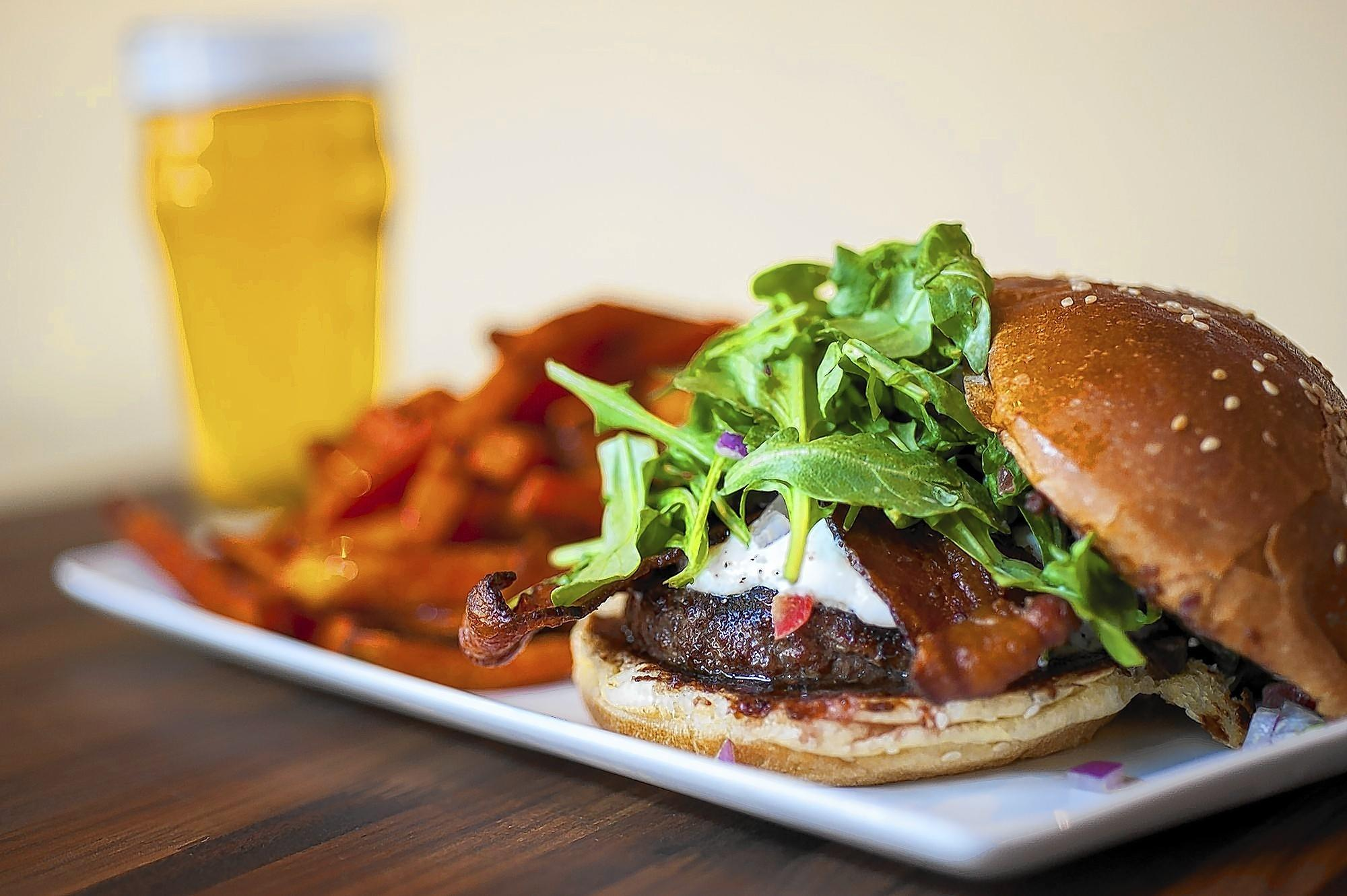 The Fresno Fig Burger includes a homemade fig marmalade, melted goat cheese, crispy bacon garnished with tomato, red onion and arugula tossed in a spicy porter mustard.