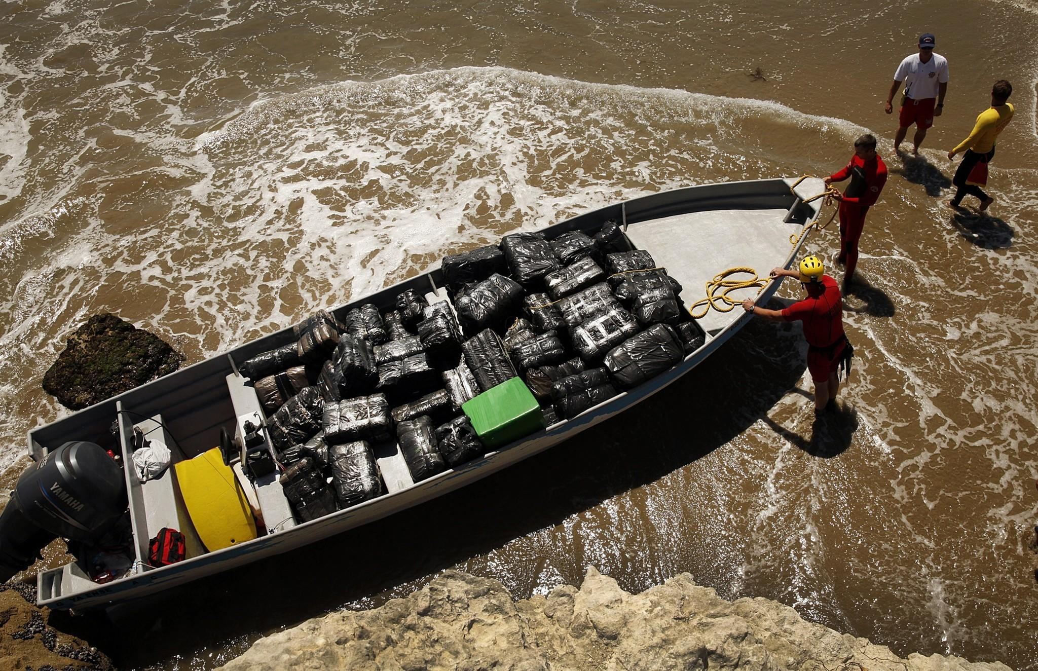 Firefighters and lifeguards inspect a beached panga-style boat that was loaded with marijuana.