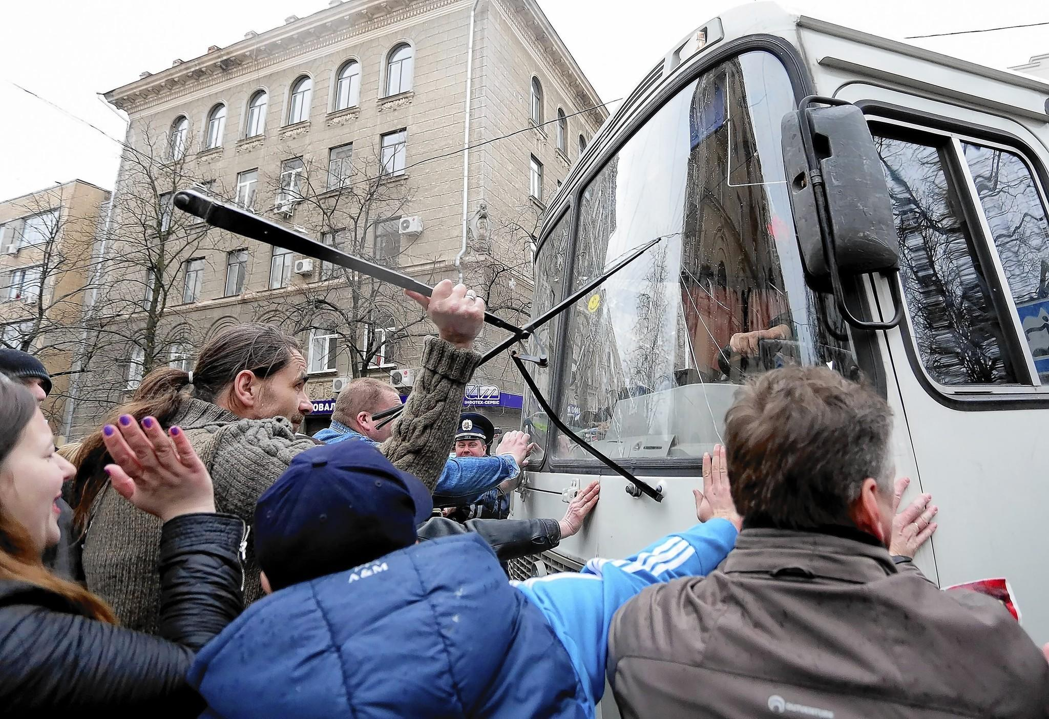 Pro-Russia demonstrators attack a police bus in Kharkiv, in eastern Ukraine.