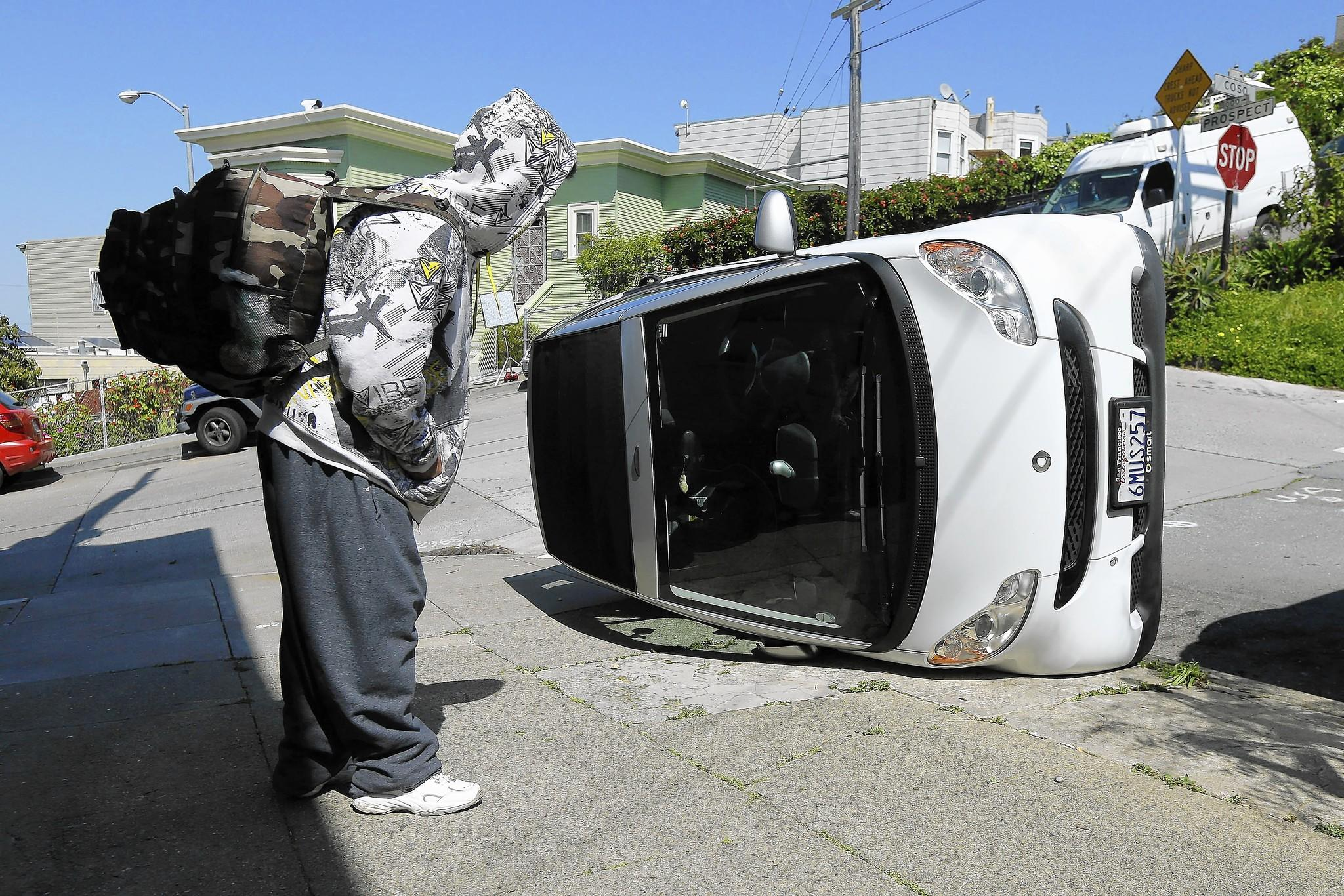 A passerby studies one of the tipped-over Smart cars in San Francisco. Police consider the four acts to be vandalism.