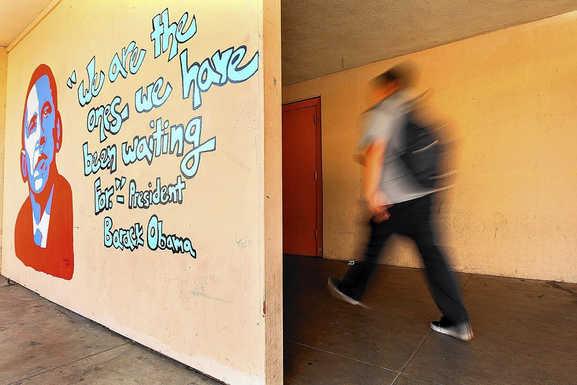 A student passes by a mural of President Obama at Markham Middle School. The lawsuit was launched after layoffs in 2009 at Markham, Gompers and Liechty middle schools.