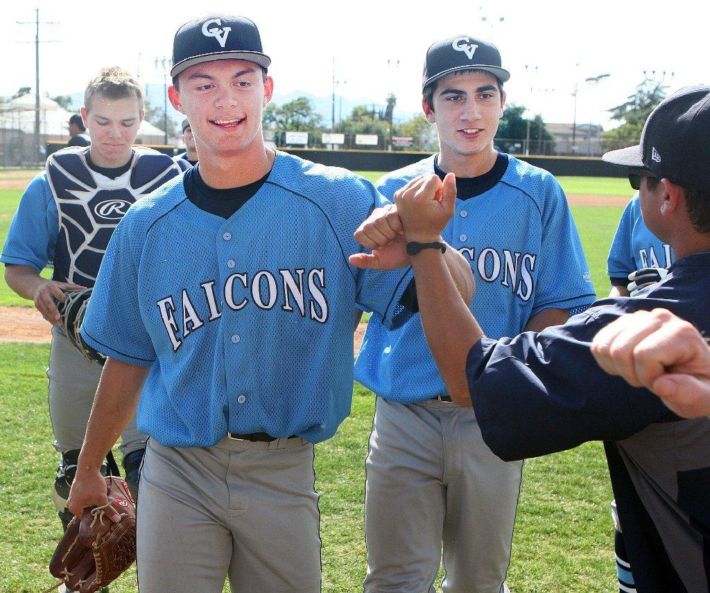 Crescenta Valley High pitcher Jimmy Smiley fist bumps with coaches and teammates after catching a line drive come-backer and then throwing out the Glendale runner at first base in a Pacific League baseball game on Tuesday. Crescenta Valley beat Glendale, 4-0. (Tim Berger/Staff Photographer)
