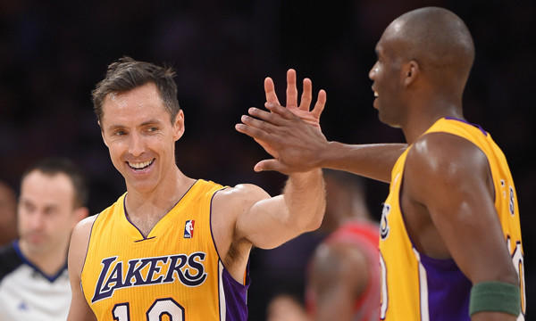 Lakers point guard Steve Nash, left, is congratulated by guard Jodie Meeks after moving into a tie for third place on the NBA's career assists list. Nash later took sole possession of third place on the list during the Lakers' 145-130 loss to the Houston Rockets.