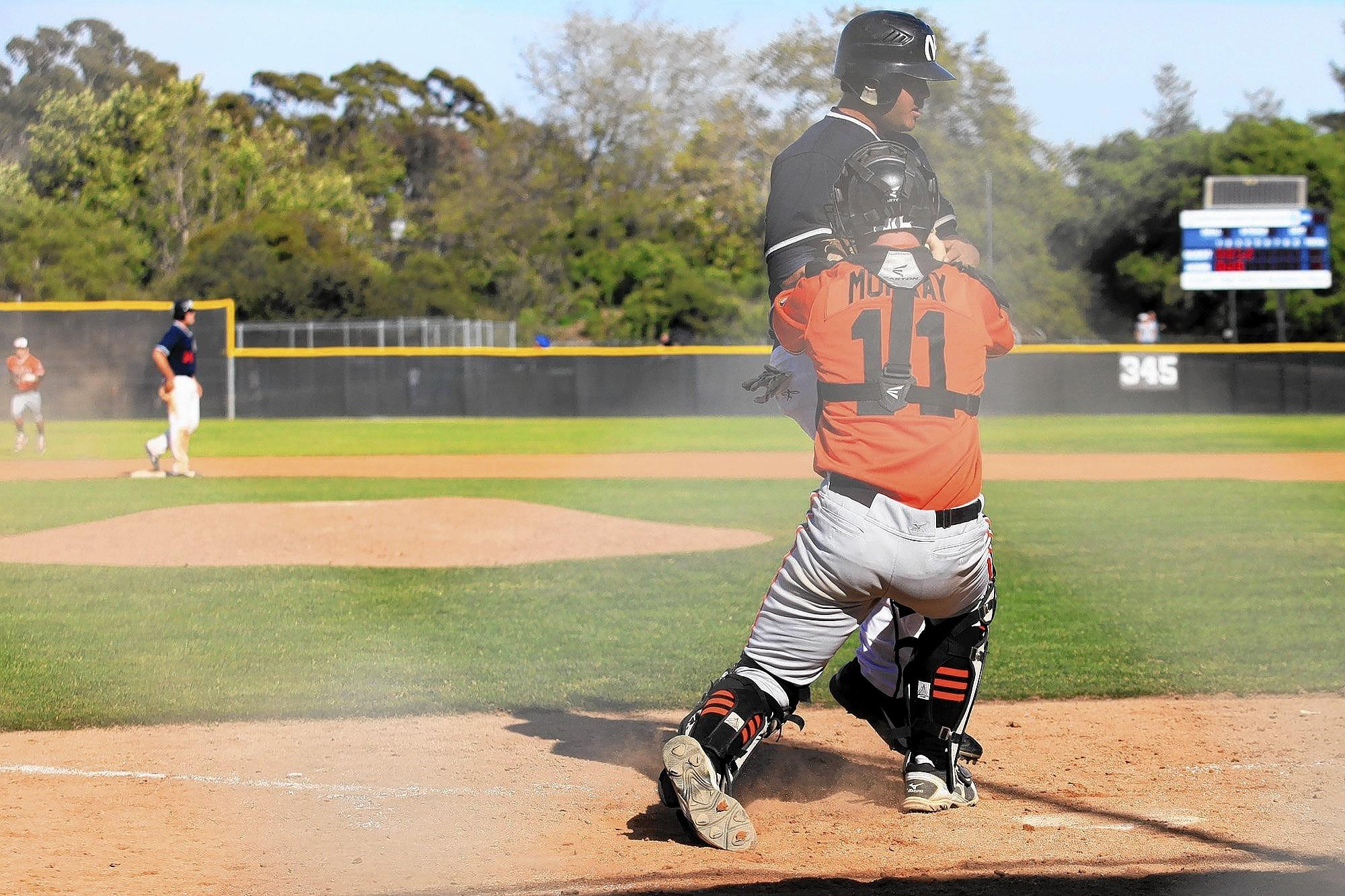 Huntington Beach High catcher Tyler Murray (11) tags out Newport Harbor's Keith Marshall completing a triple play to close out the fourth inning in a Sunset League game on Tuesday.