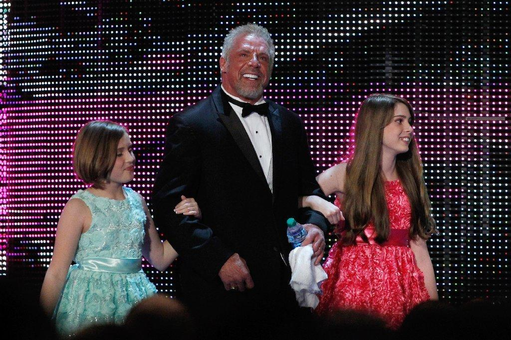 The Ultimate Warrior is escorted by his daughters to the stage during the WWE Hall of Fame induction ceremony in New Orleans on Saturday.