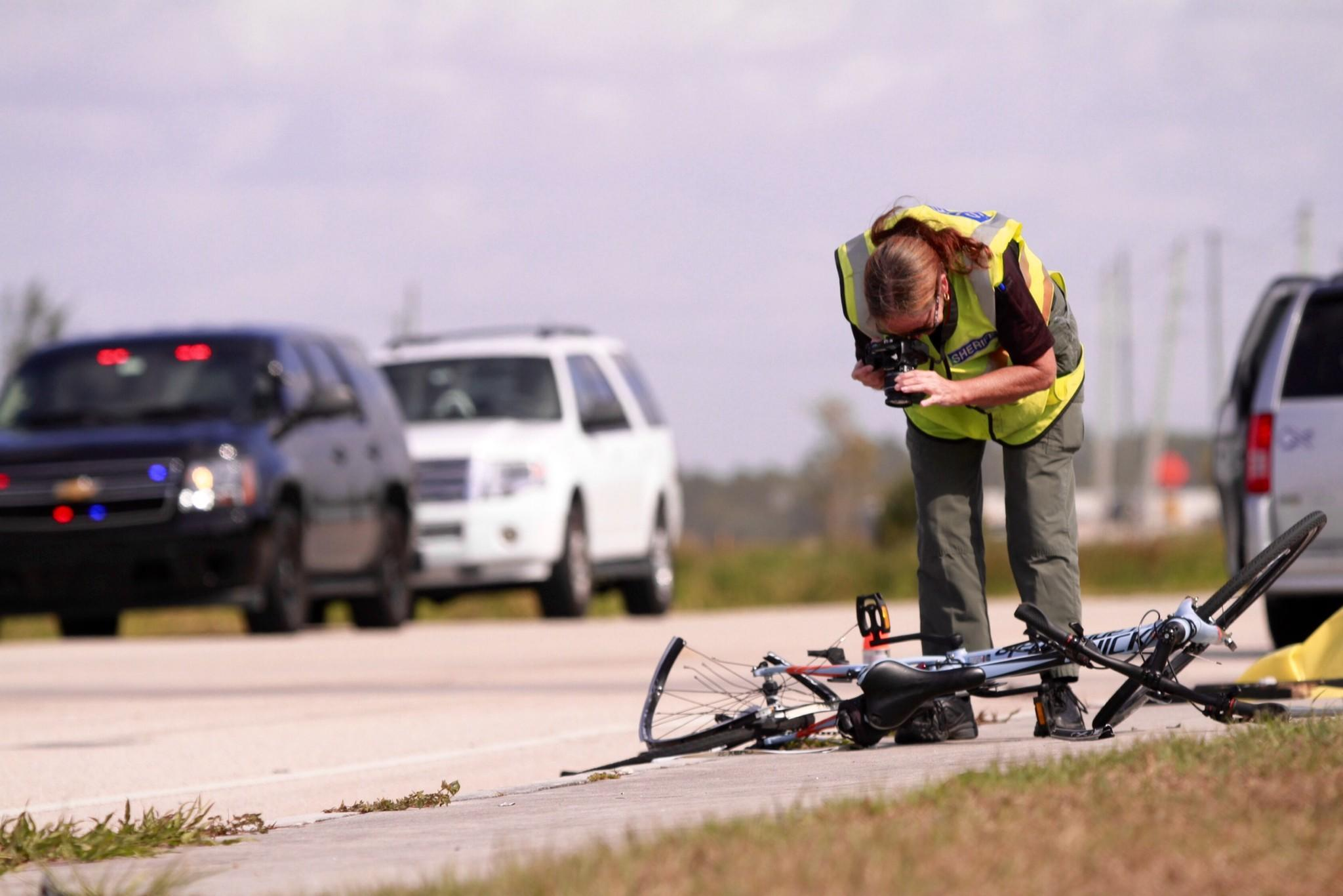 A Palm Beach County Sheriff's Office crime scene investigator photographs a bicycle at the scene of a fatal vehicle vs. bicycle crash on Lyons Road north of Clint Moore Road on Wednesday.