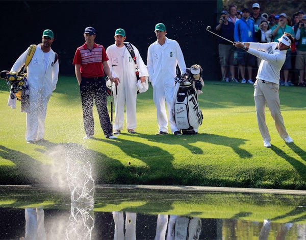 Bubba Watson skips a shot on the pond at the 16th hole as Webb Simpson and their caddies look on during a practice round Wednesday ahead of the Masters at Augusta National.