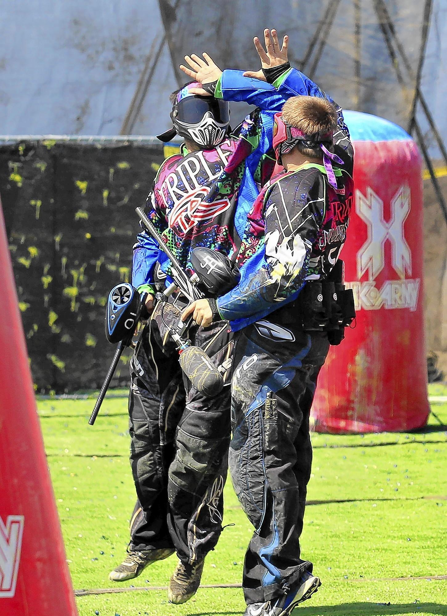 David Mount, left, and Jared Long, right, celebrate after beating opponents Alexander Mitchell and Heather Harvey, not pictured, during a 2 on 2 match at the Surf City Paintball Open near Huntington Beach Pier on Saturday.