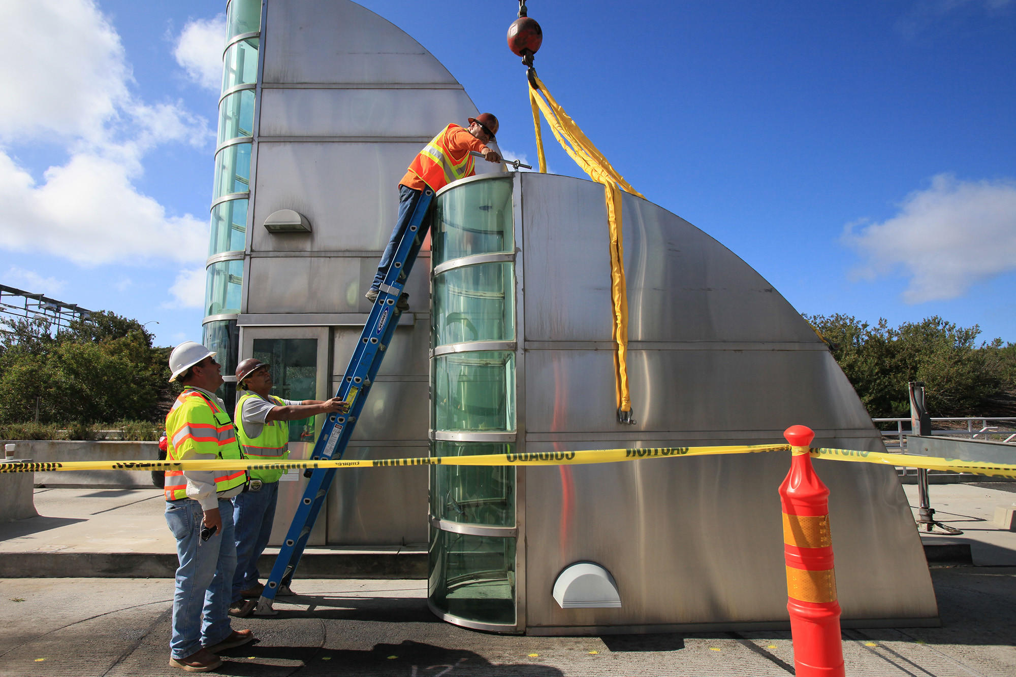Employees from Ortiz Enterprises prepare to move the top half of a toll booth onto of a truck bed at Catalina View Mainline Toll Plaza along California State Route 73.