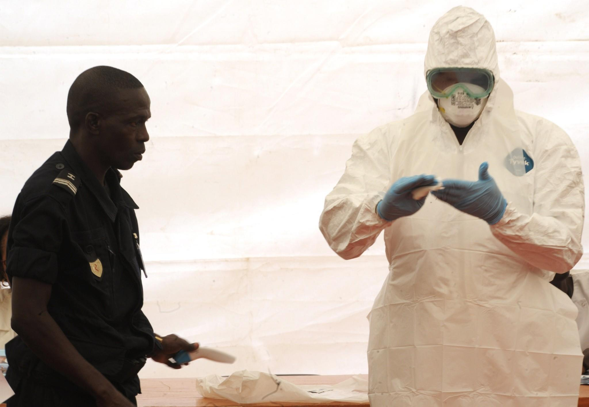 A Senegalese hygienist demonstrates how to protect oneself against the Ebola virus at Dakar airport, during a visit of the Senegalese health minister to check the safety measures put in place.
