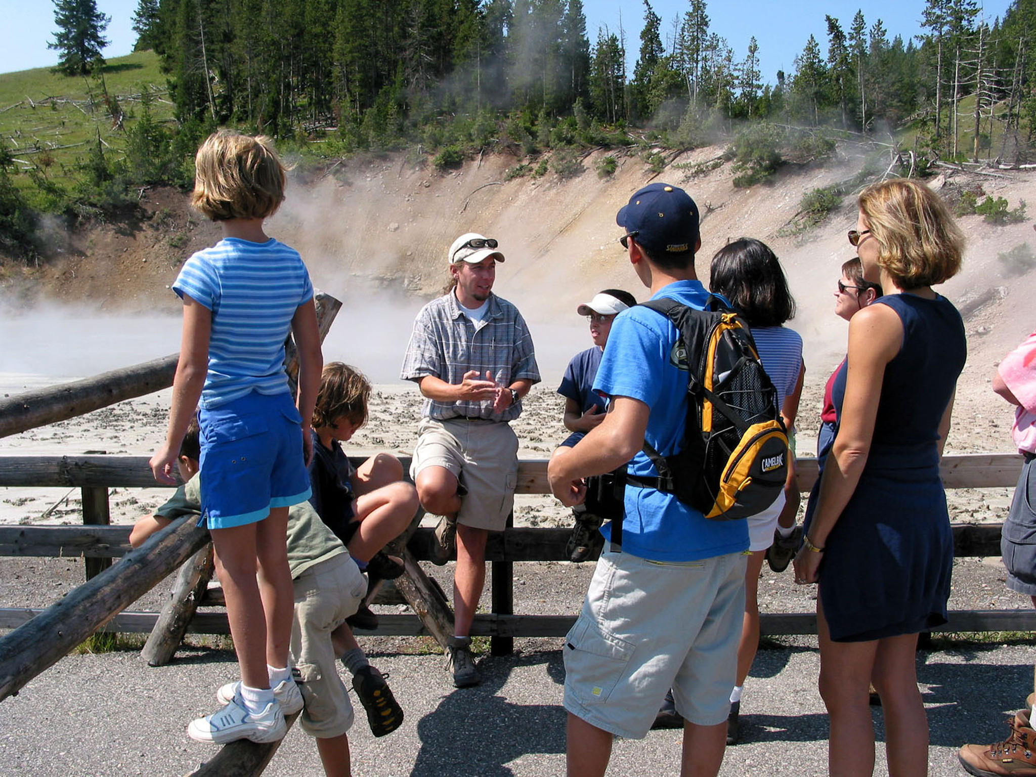 A guide talks with families about thermal goings-ons at Yellowstone National Park.