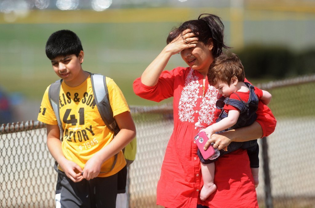 Erum Naqvi holds her son Ayan as she picks up her son Raza Naqvi, left, after a stabbing rampage at Franklin Regional Senior High School in Murrysville, Pa.