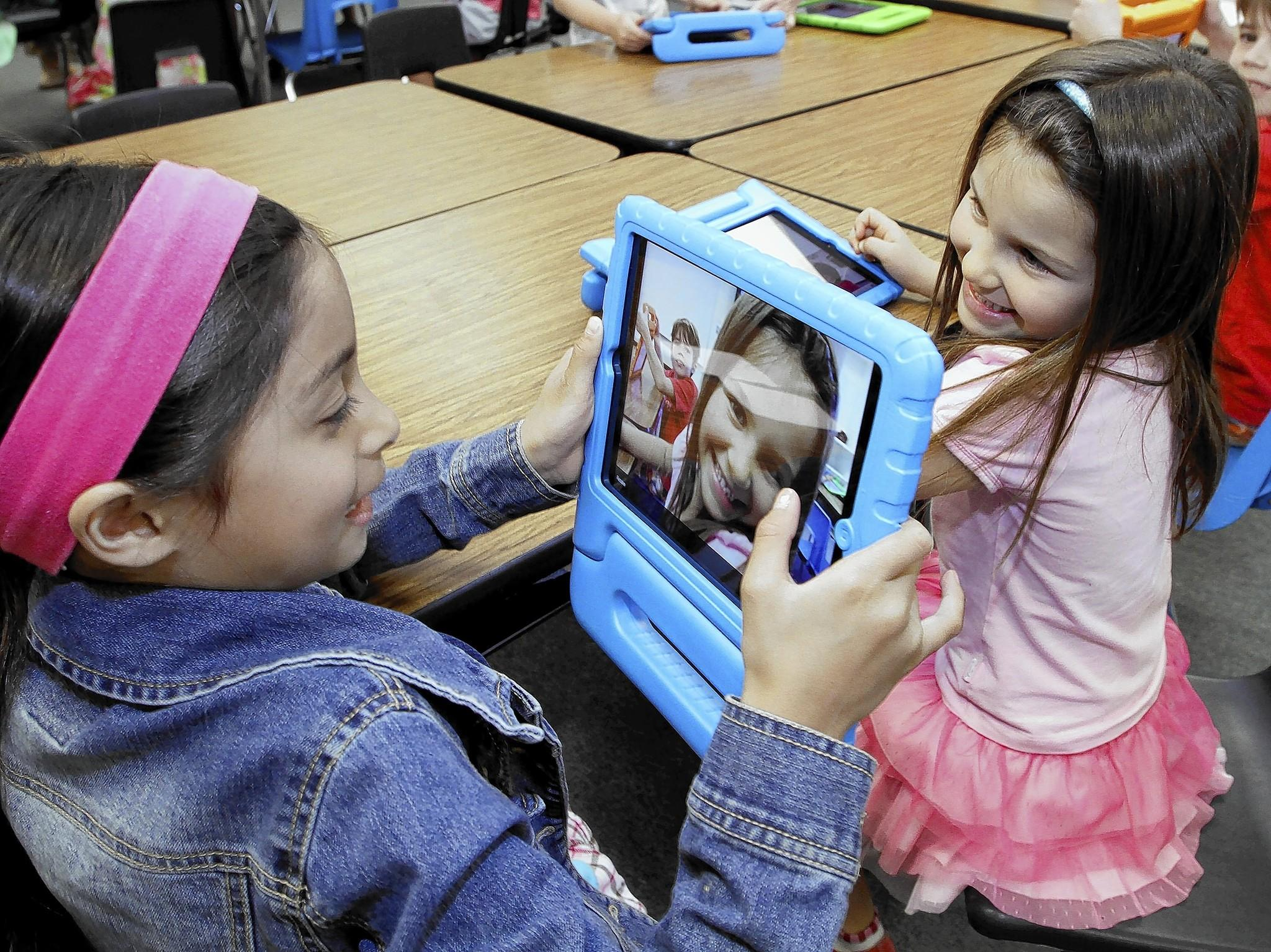 First grader Lexi Frost, left, takes a photo of her friend Kate Cooper, right, during class at Palm Crest Elementary School's iPad Learning Lab in La Cañada Flintridge on Tuesday, April 8, 2014. The school district recently opened three elementary school iPad Learning Labs with donations from the Educational Foundation.