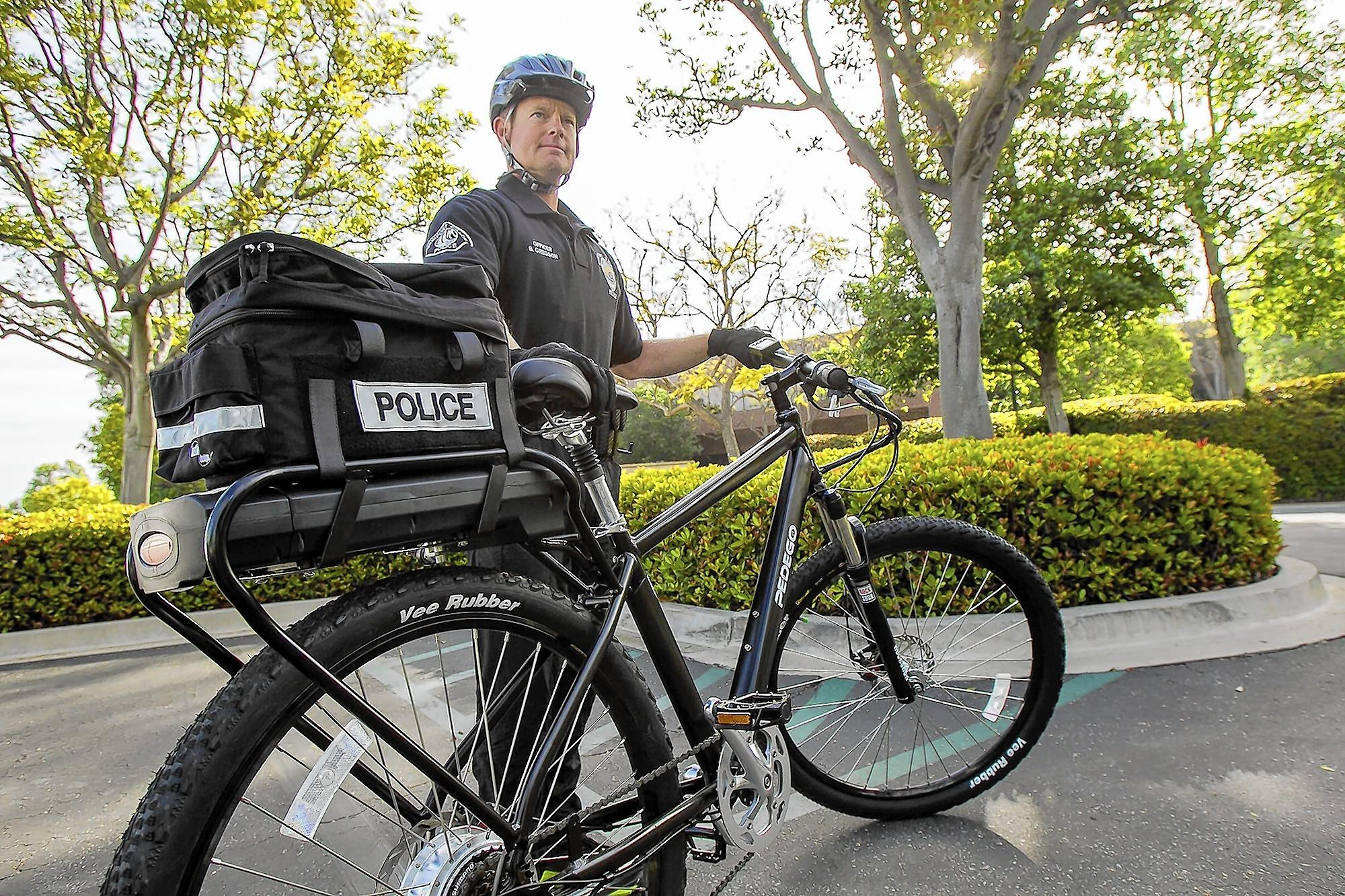 Officer Bryan Gregson with the Newport Beach Police Department shows off one of two electric bikes that the department has purchased for use on patrols of the peninsula.
