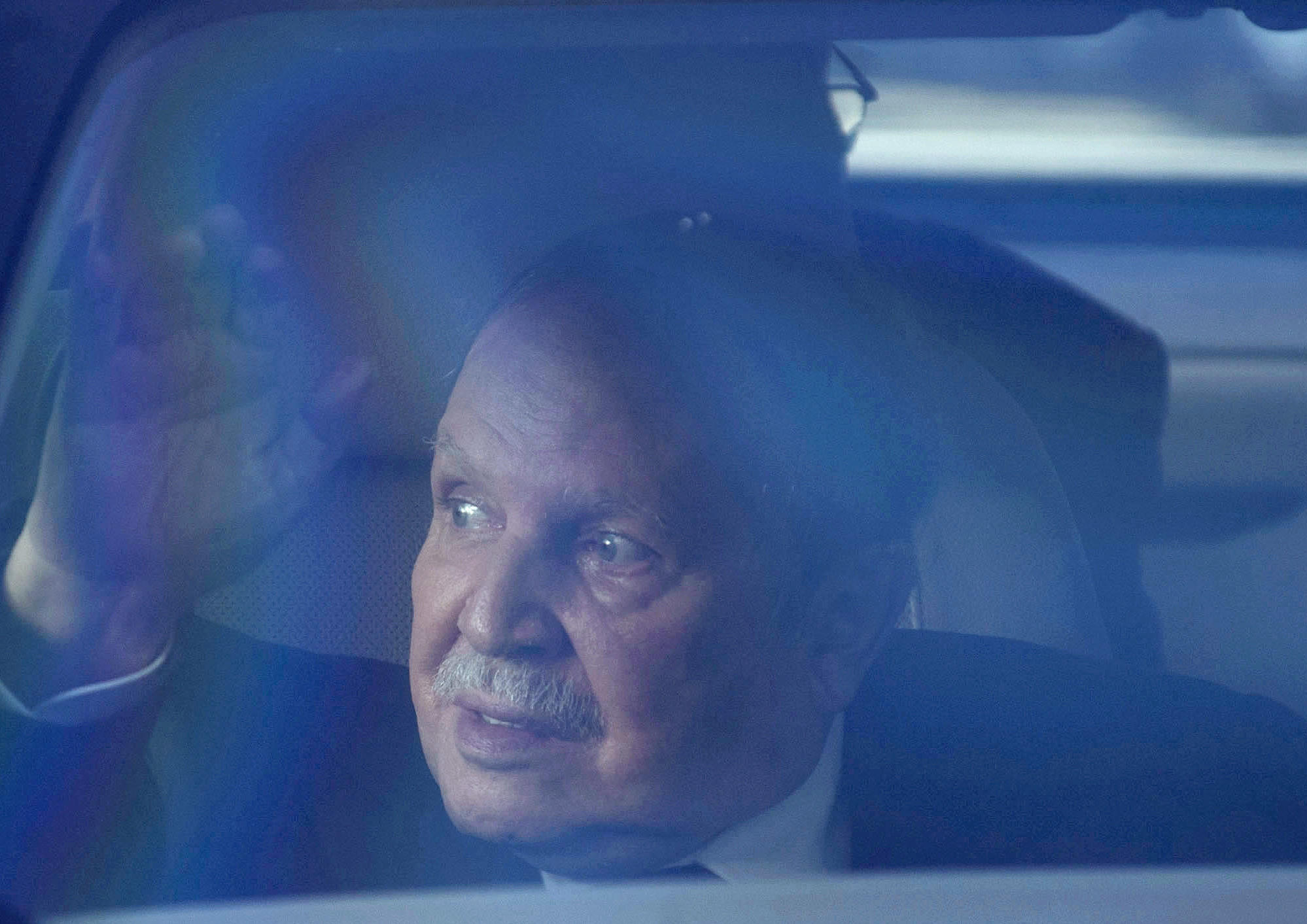 Algerian President Abdelaziz Bouteflika waves from inside a vehicle on March 3, 2014, in Algiers.