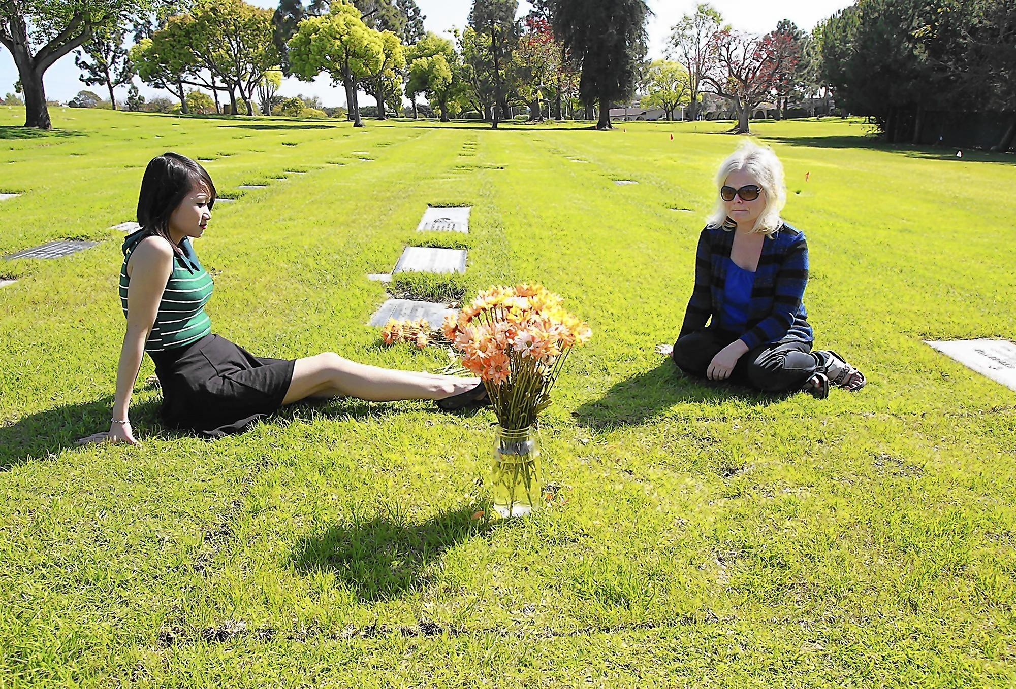 Ivy Ho, left, and Melissa Ludlow pause and share stories about Jon Ludlow at his gravesite at Pacific View Memorial Park in Newport Beach.