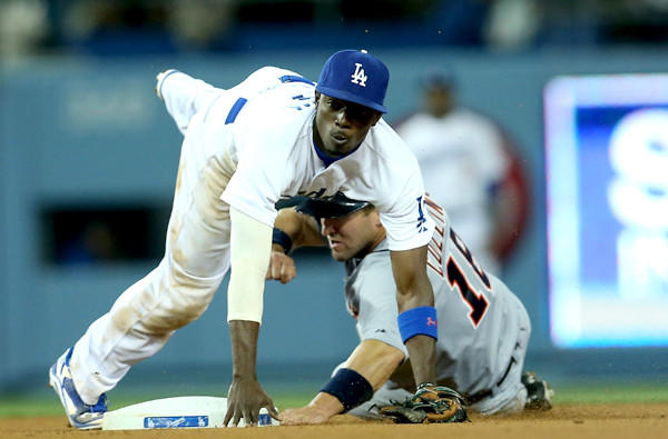 Dodgers second baseman Dee Gordon tumbles over Detroit's Tyler Collins after making a throw to first base to complete a double play in the eighth inning Wednesday night at Dodger Stadium.