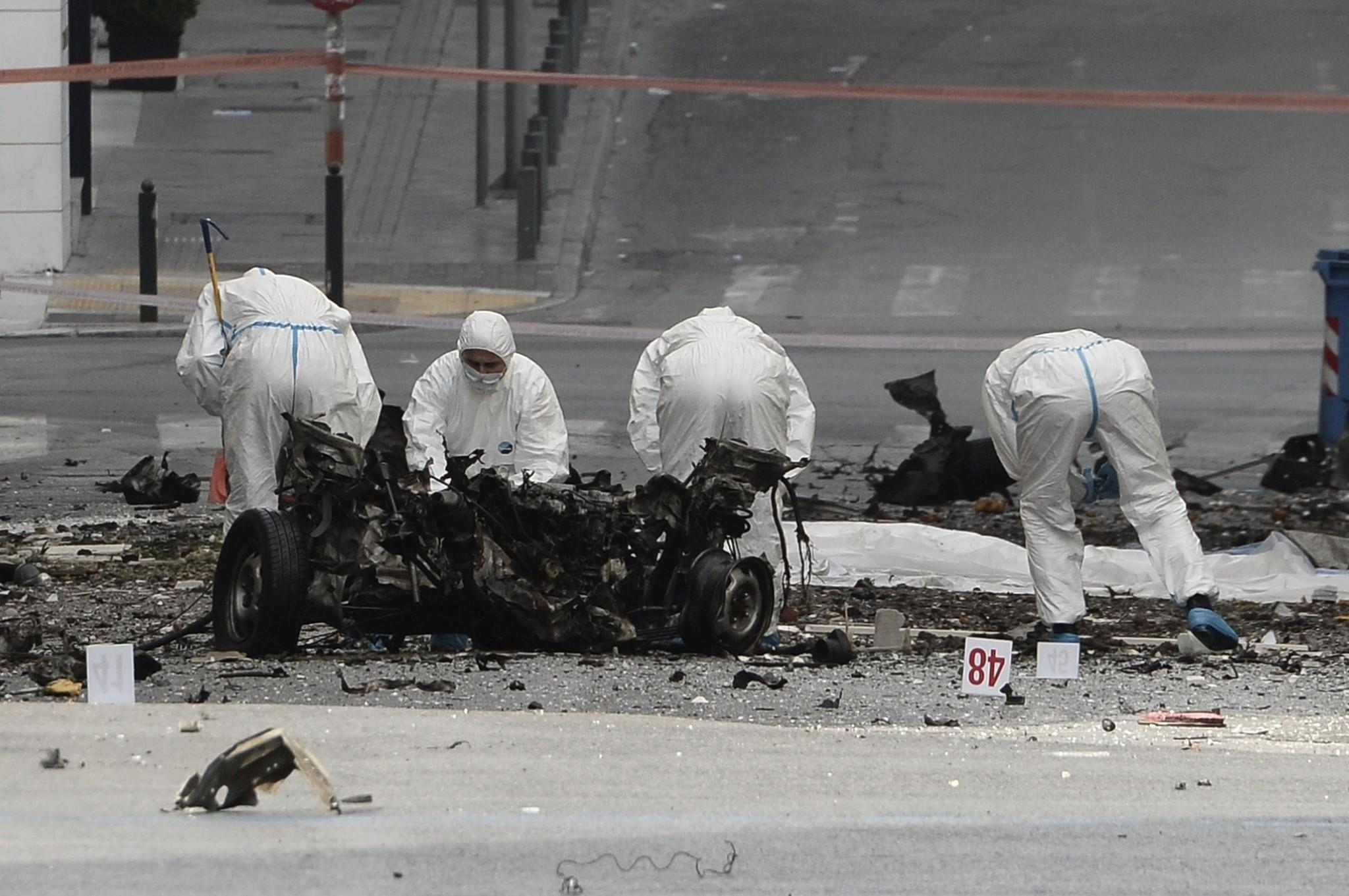 Police search the wreckage of a booby-trapped car that exploded outside the Bank of Greece in Athens.