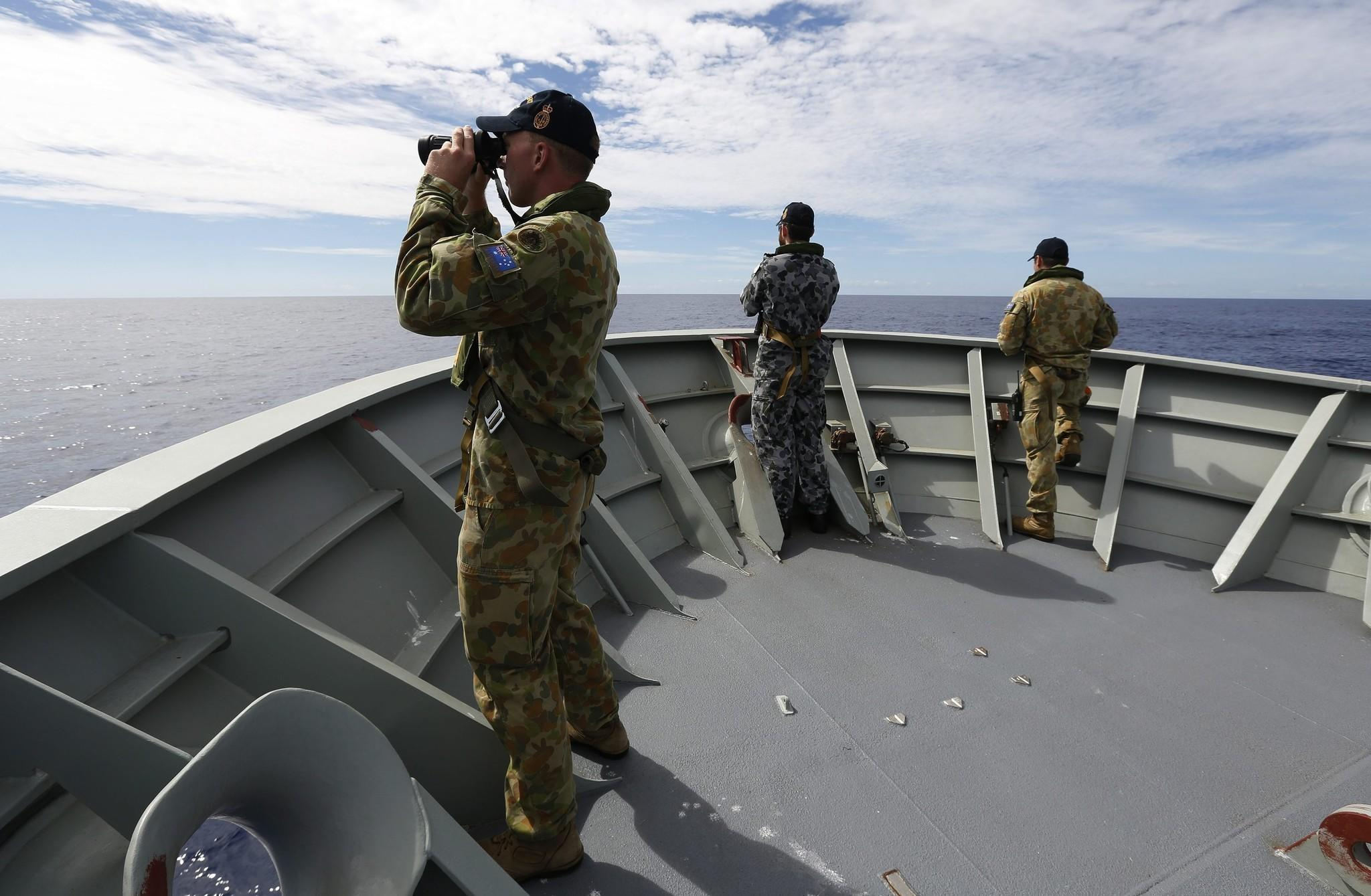 Australian Defense Force personnel aboard the Royal Australian Navy ship Perth search for debris from missing Malaysia Airlines Flight 370.