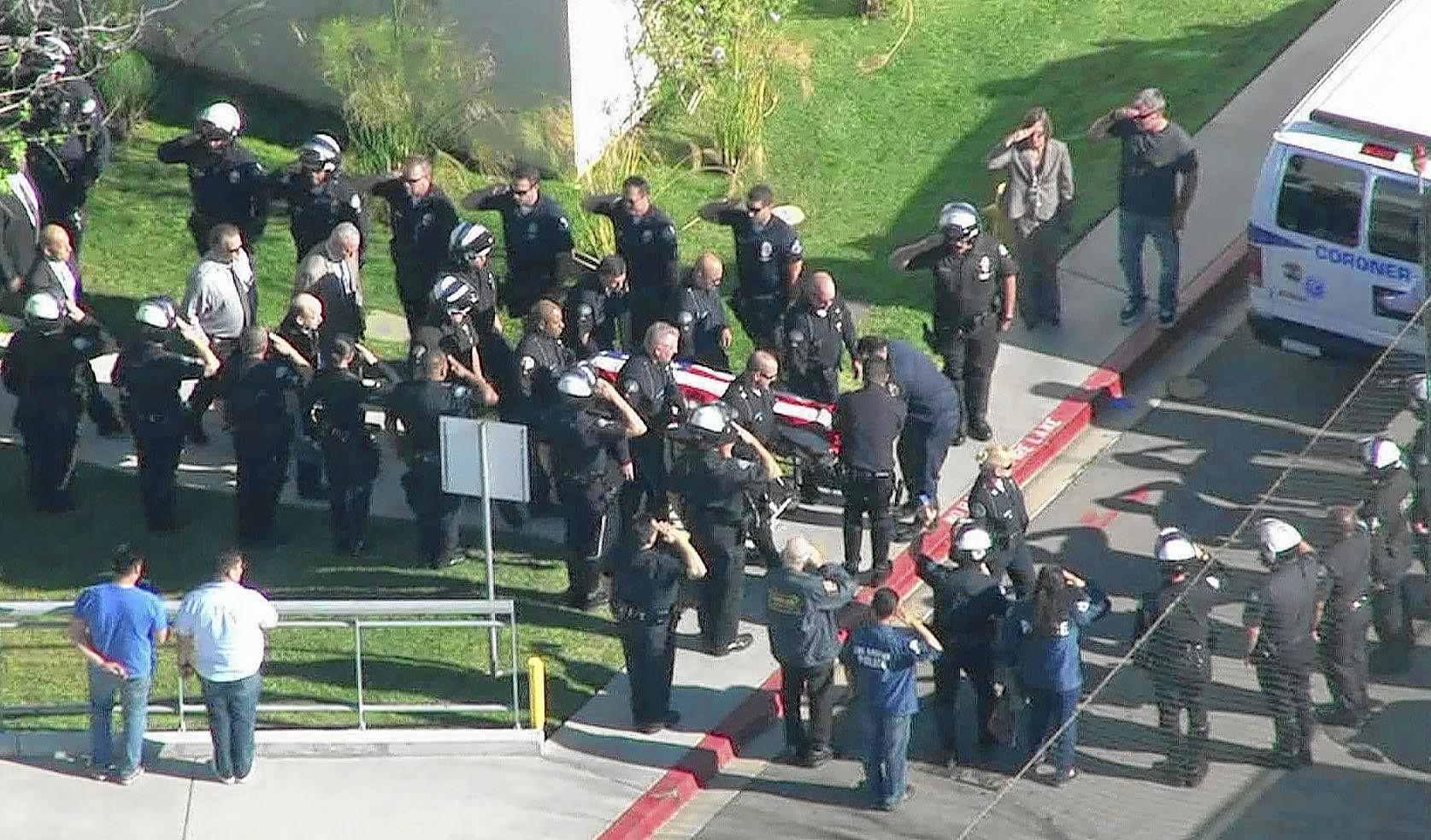 LAPD officers salute as the body of Officer Chris Cortijo passes by before heading to the L.A. County morgue with a police escort.