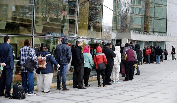People wait in line to enter a job fair at the Arena Stage in Washington.