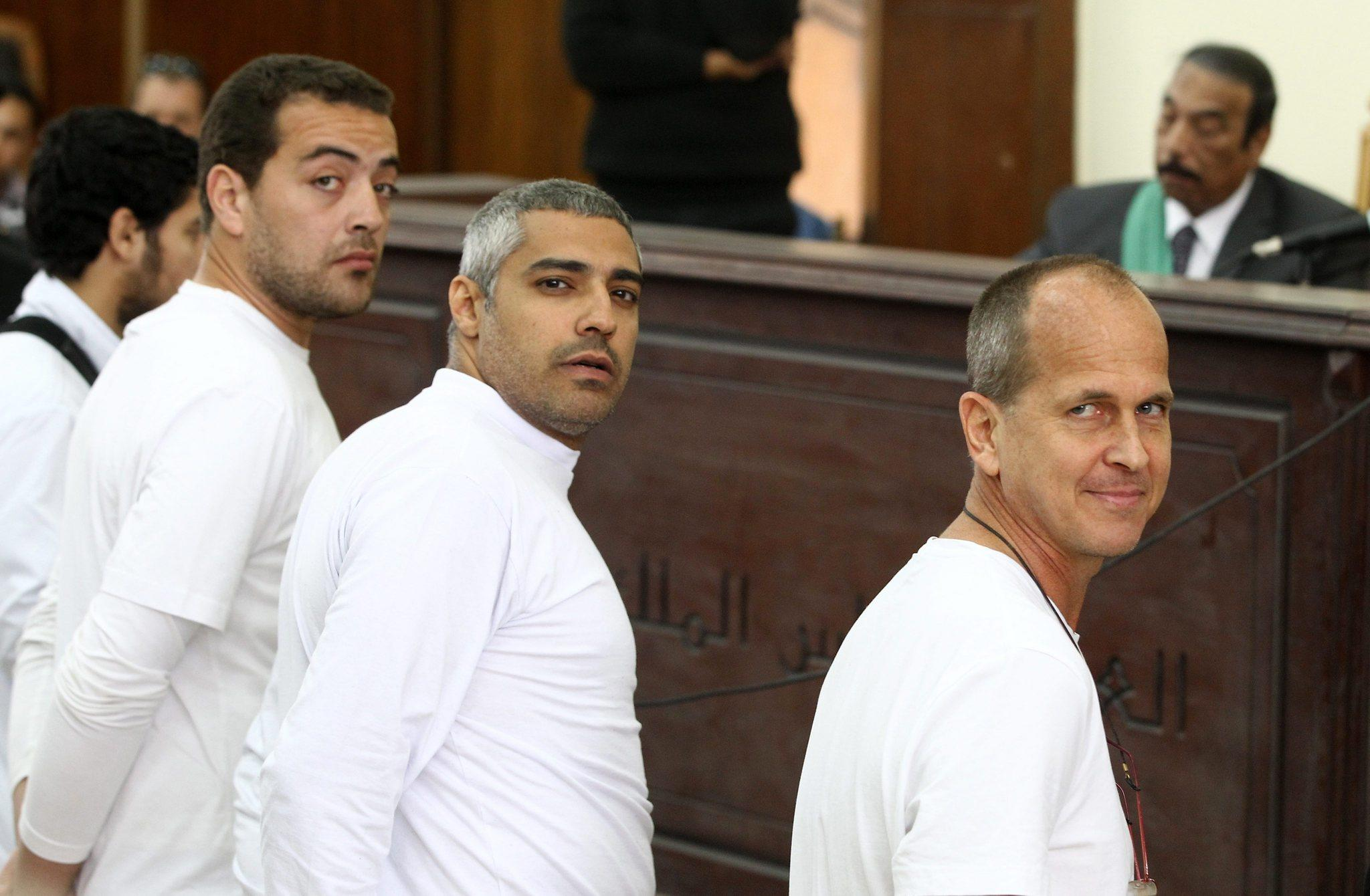 Australian journalist Peter Greste, right, and co-defendants stand in front of the judge's bench in Cairo on March 31 during their trial for allegedly supporting a terrorist group and spreading false information.