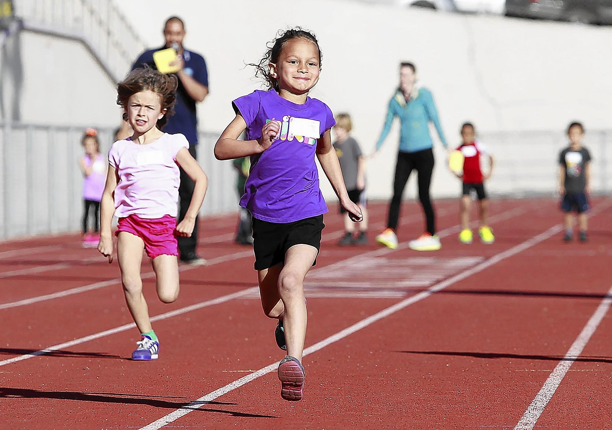 Sienna Brown smiles as she pulls away during the 50-meter run during the Laguna Beach Community Service Department's annual Youth Track Meet at Laguna Beach High School on Friday.