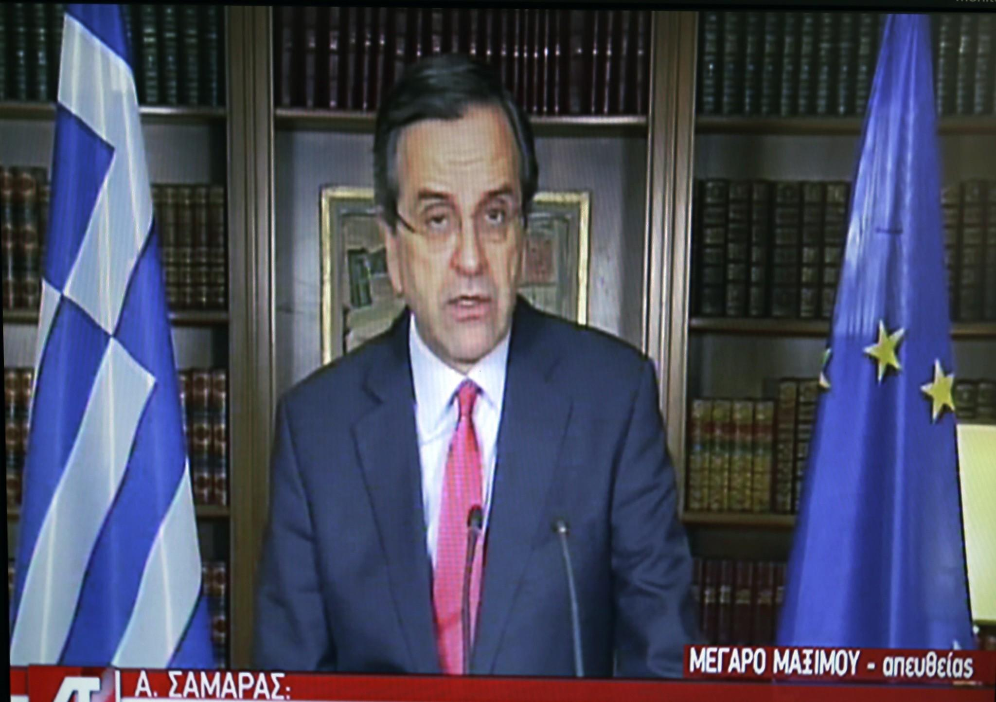 In this image taken from State TV, Greece's Prime Minister Antonis Samaras remarks on the bond sale from his office in Athens.