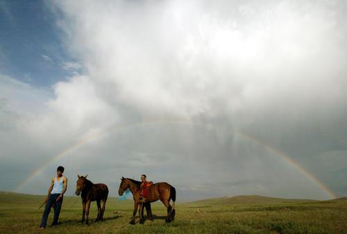 Mongolian nomads train horses under a rainbow at Khui Doloon Khudag village.