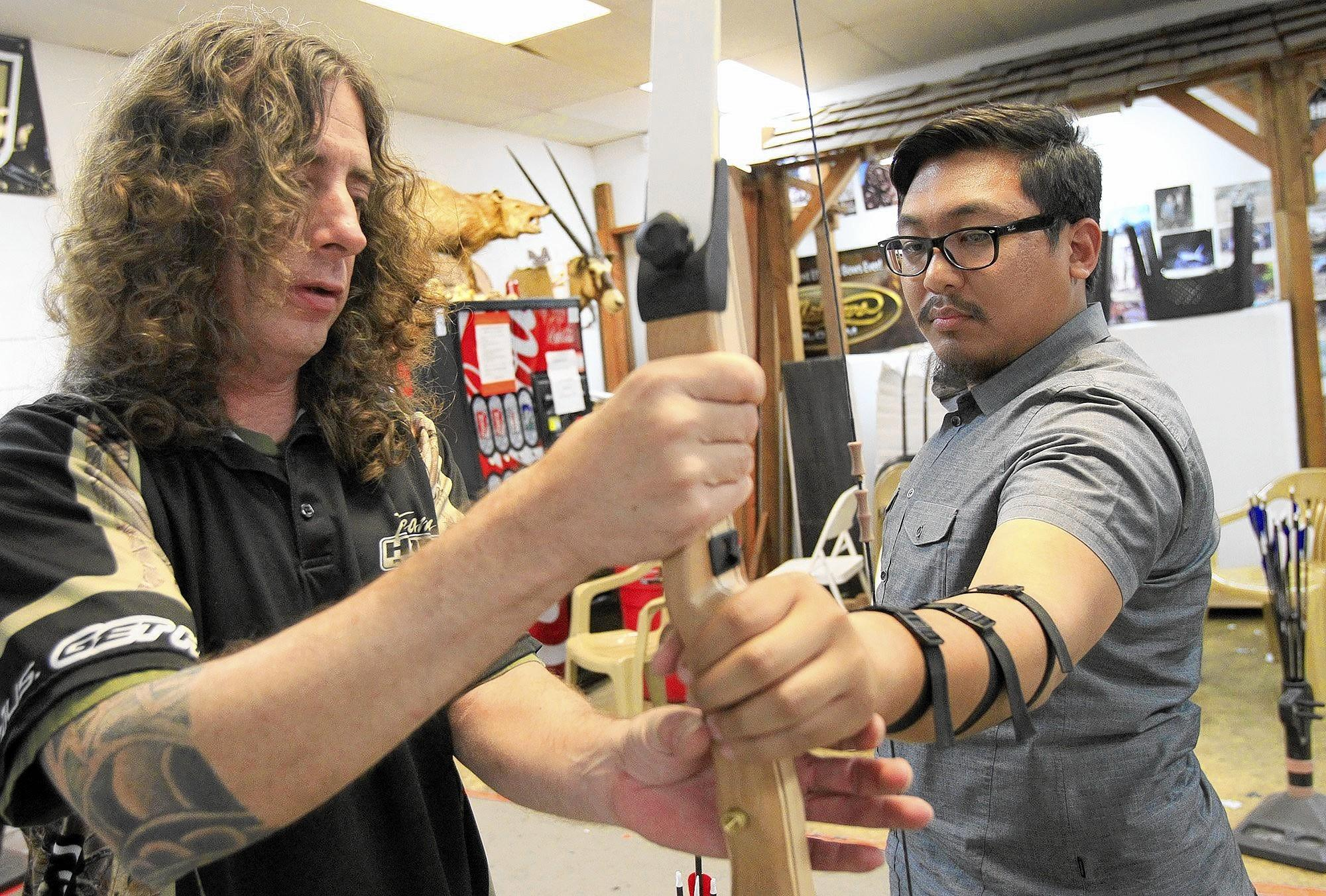 Manager Kevin Clark, left, instructs HB Independent reporter Anthony Clark Carpio on where to position his hands on a bow at Orange County Archery in Fountain Valley on Friday.