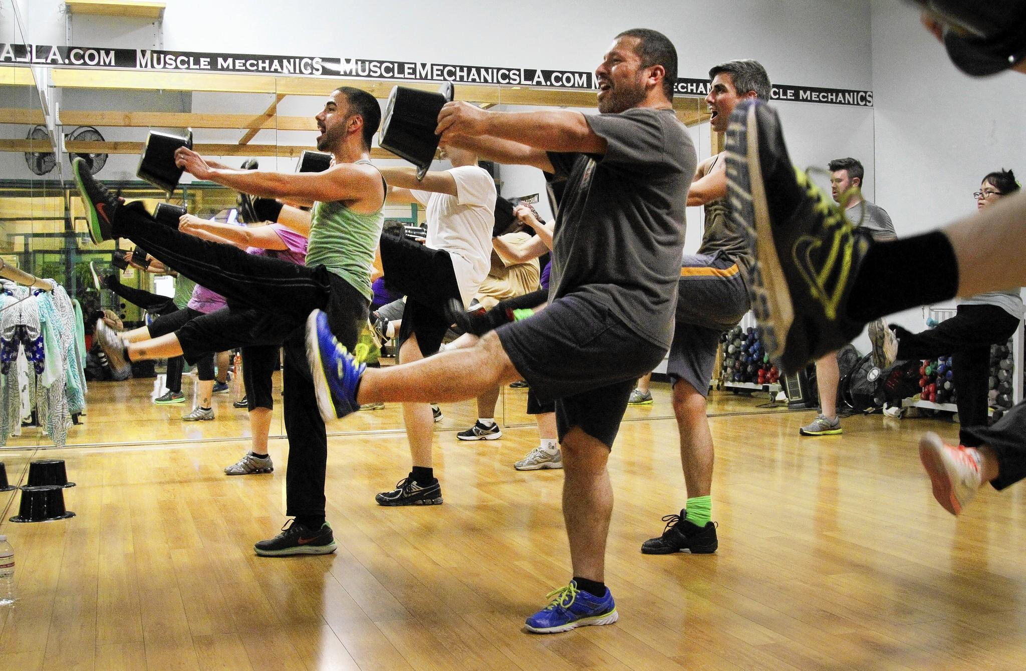 Joseph Corella, in green, leads a Broadway Bodies L.A. class — one of many different types of exercise instruction that incorporate yoga, music, interval training and more.